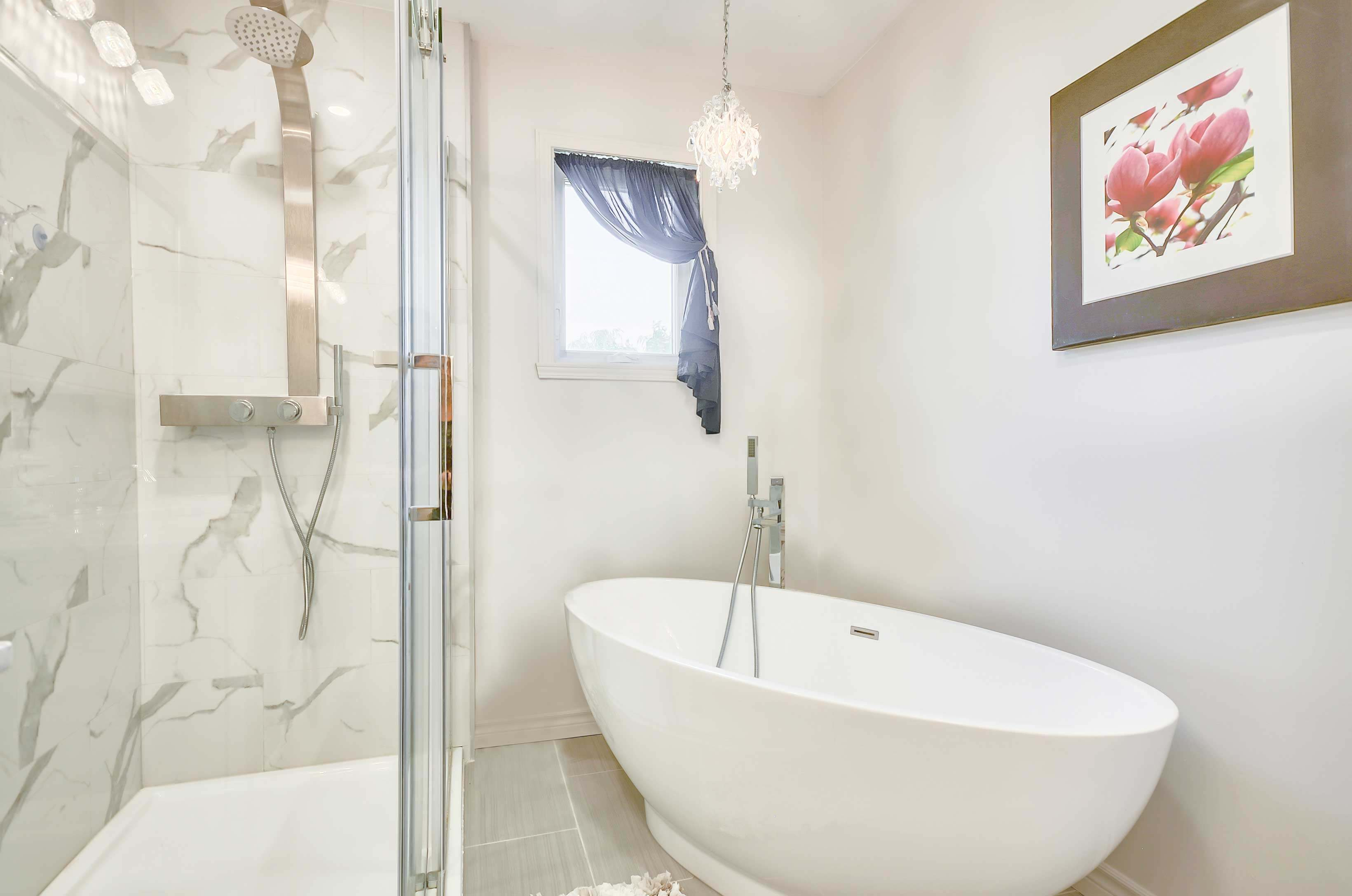 classic bathroom newly remodeled with a white freestanding bath and a glass shower