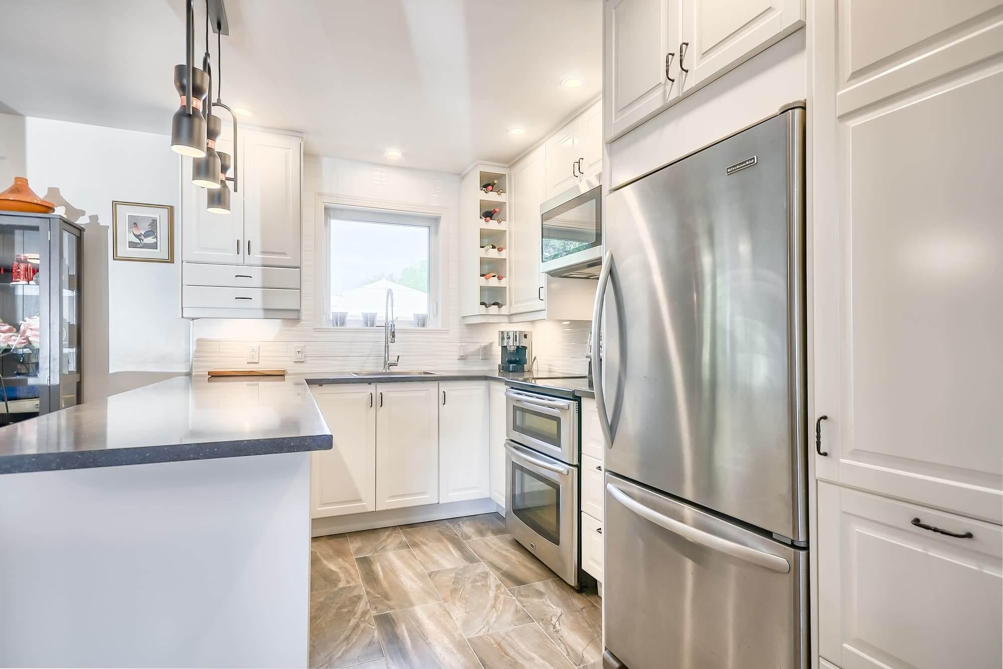 petite cuisine avec armoires blanches et comptoir en quartz gris foncé