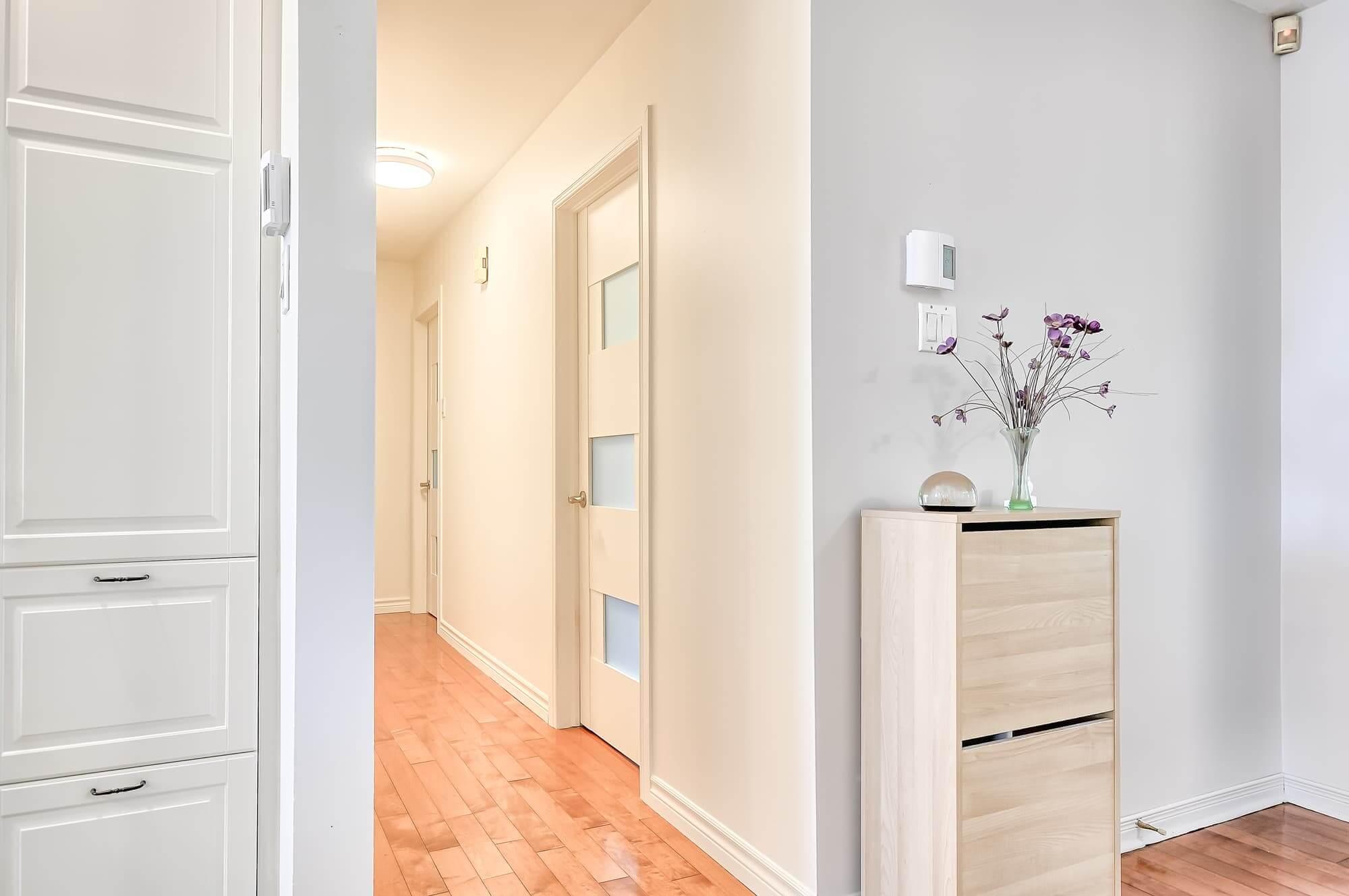 portes vitrées blanches dans passage avec plancher en bois franc et commode blanche