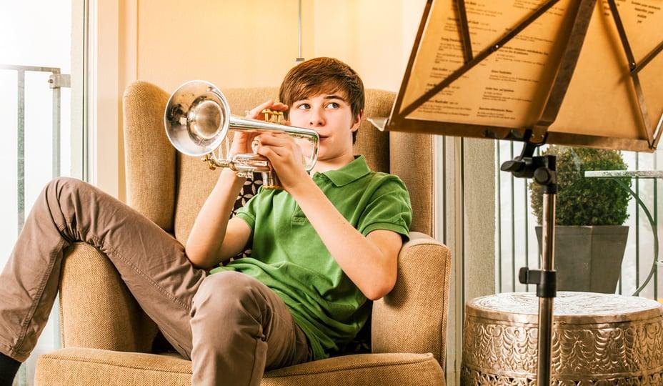 adolescent jouant de la trompette assis dans un fauteuil