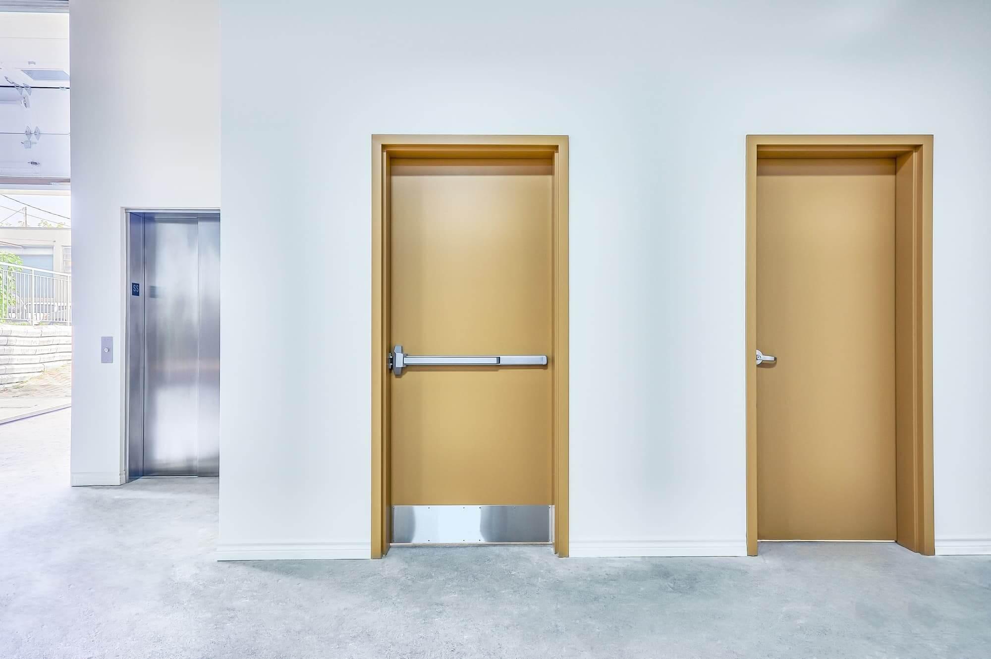 Ascenseur commercial avec porte en stainless + 2 portes jaunes dans la pièce