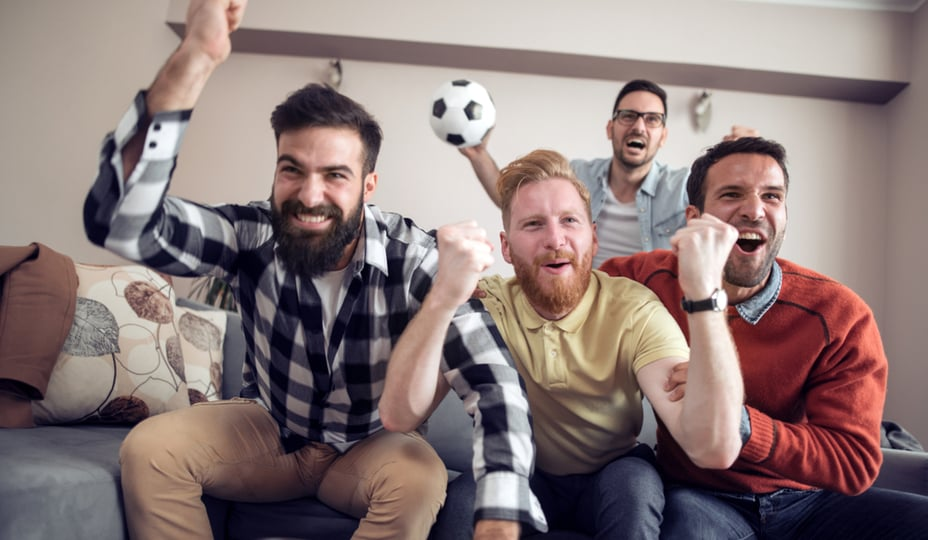 4 men watching soccer in a basement