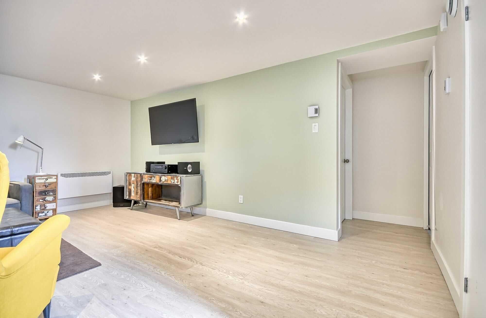 aménagement de sous-sol avec plancher flottant beige pâle, mur vert menthe et meuble ne bois avec téléviseur