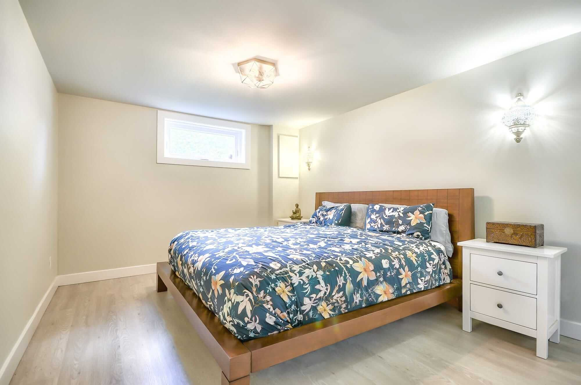 basement bedroom with a wooden bed and a white nightstand