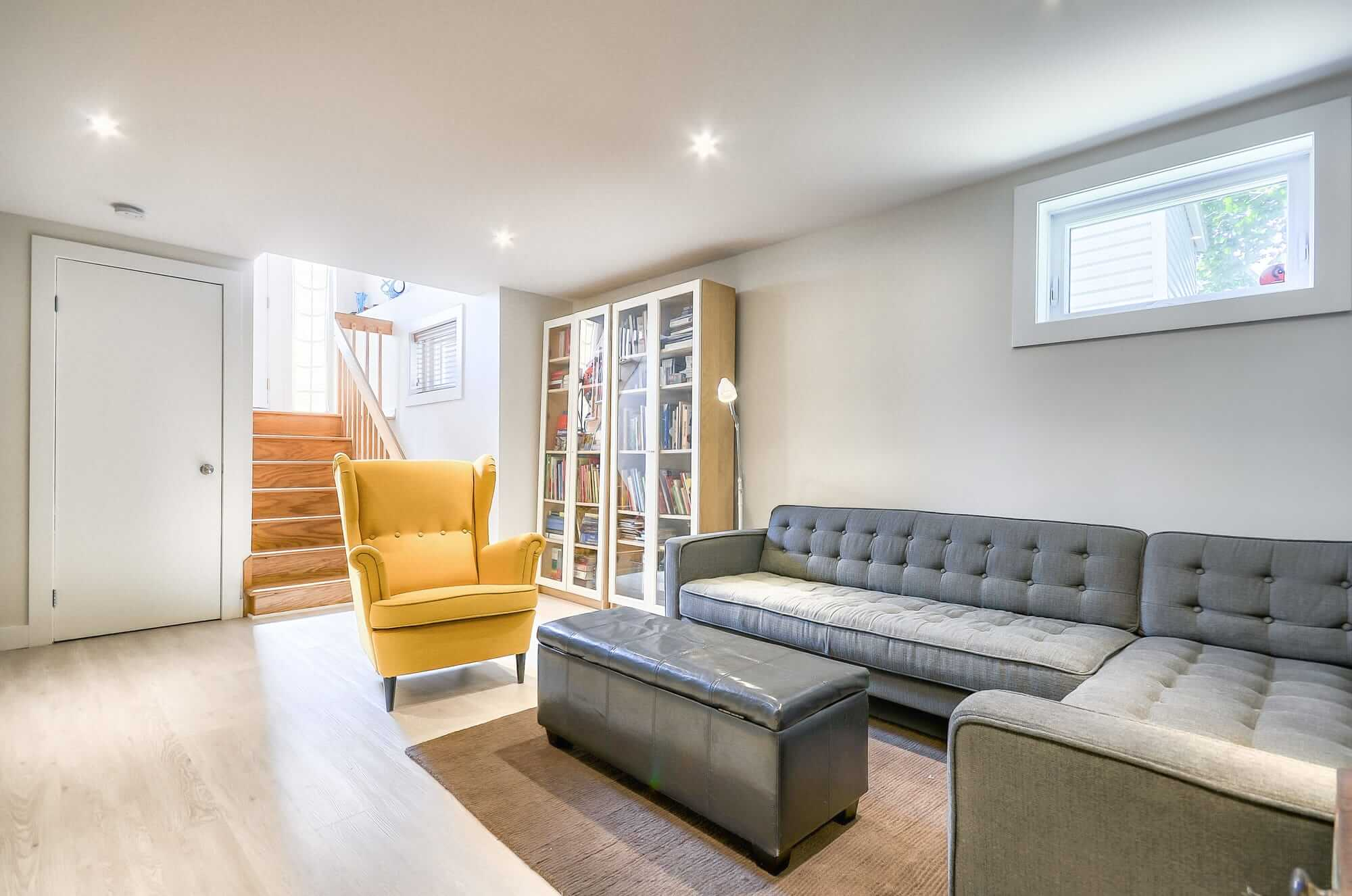 basement living room with a yellow armchair and a grey couch
