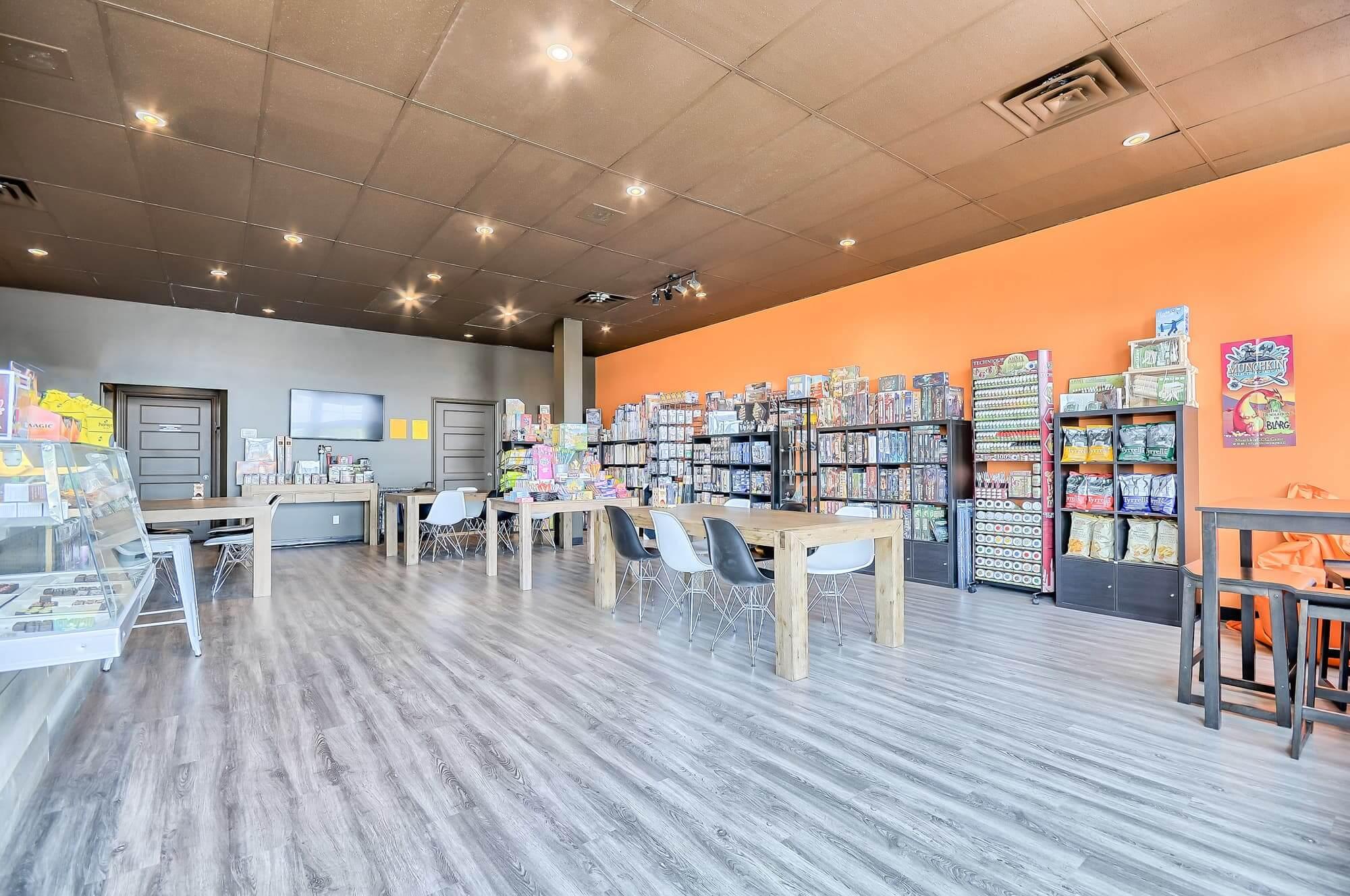 boutique et salon de jeux de société nouvellement aménagé avec plancher flottant gris et mur d'accent orange