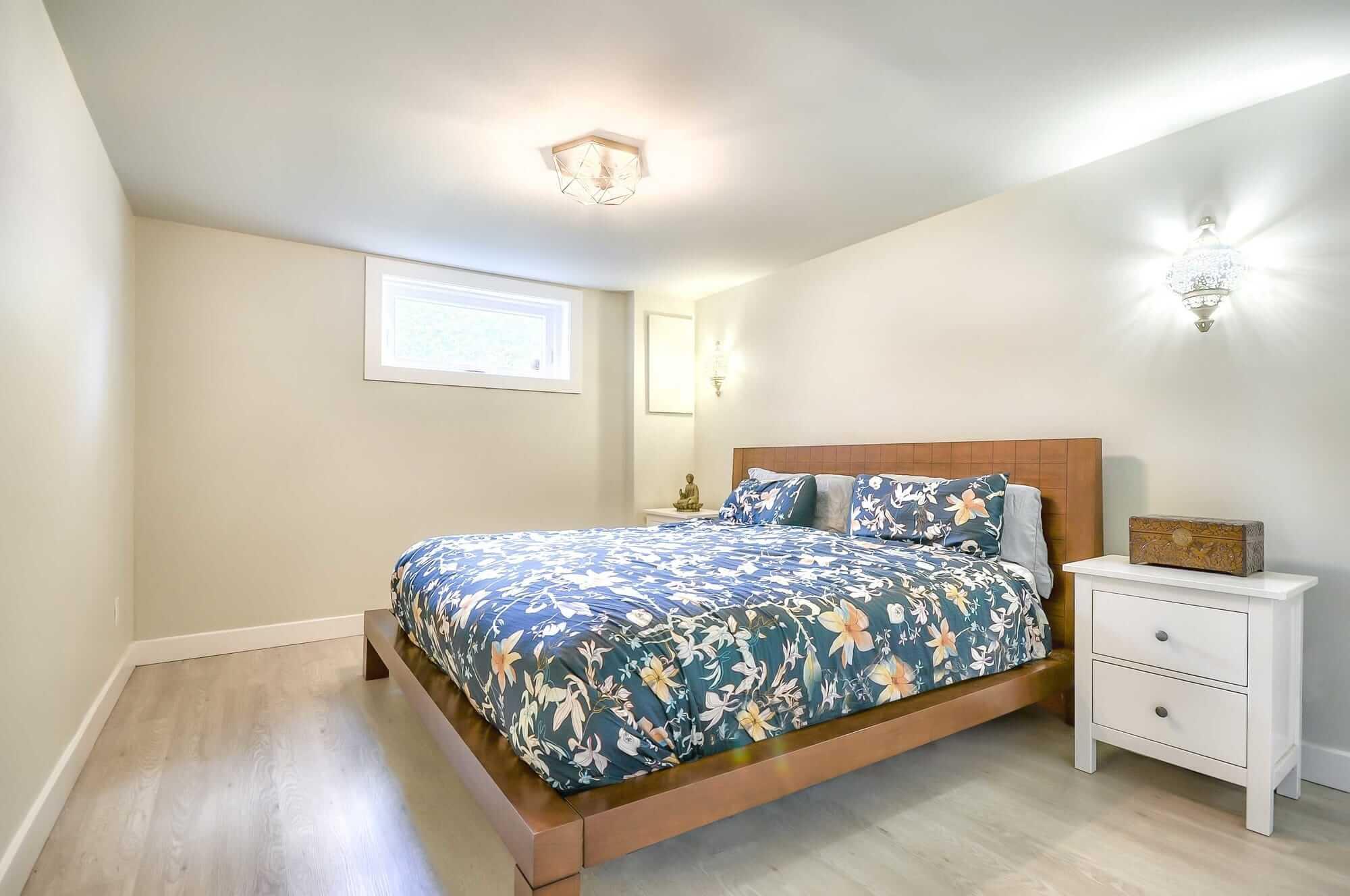 chambre au sous-sol avec lit moderne en bois et table de chevet blanche