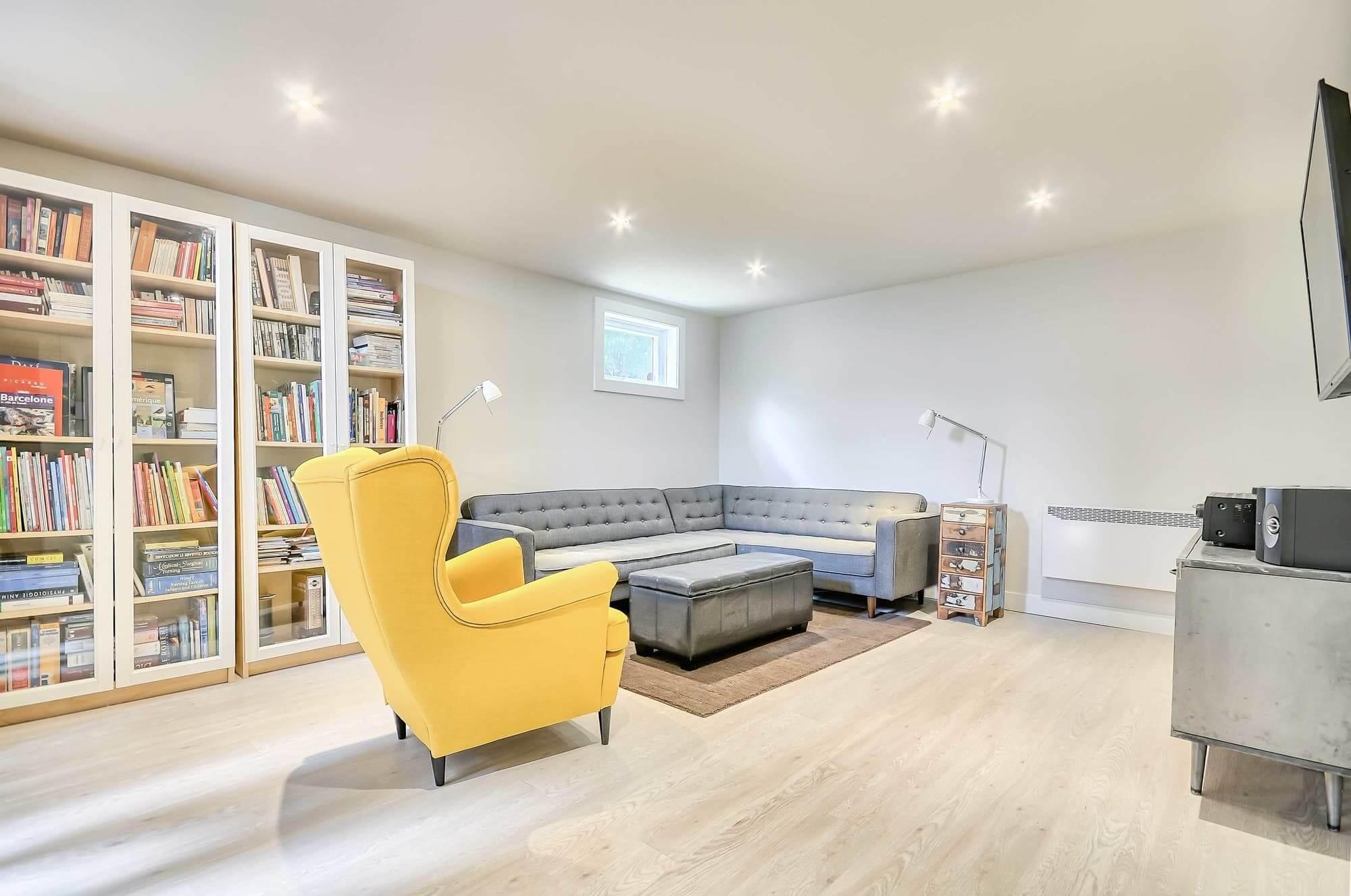décoration de sous-sol avec bibliothèque, chaise jaune et divan en L gris