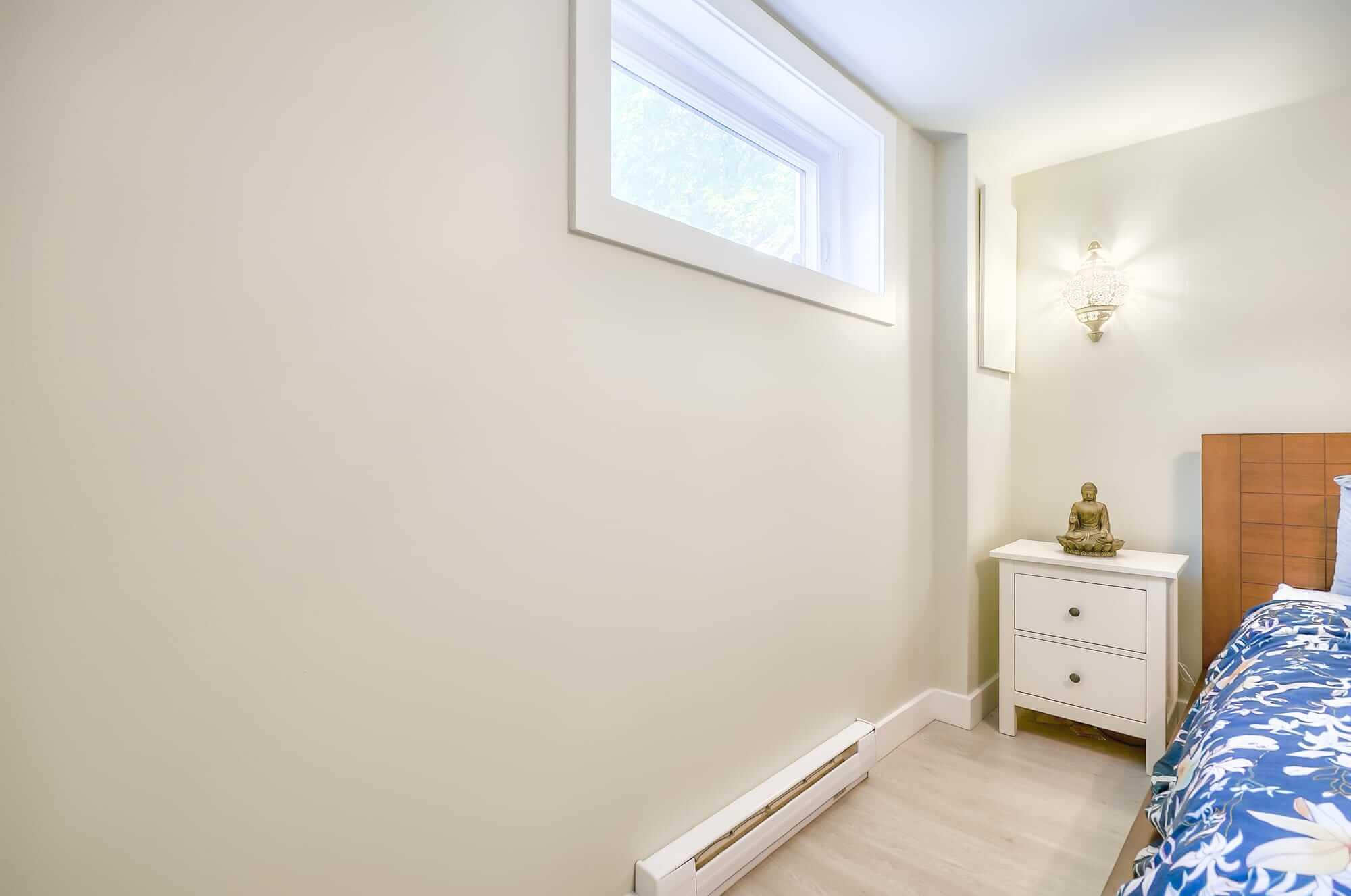 fenêtre sous-sol avec vue sur mur beige pâle et table de nuit blanche
