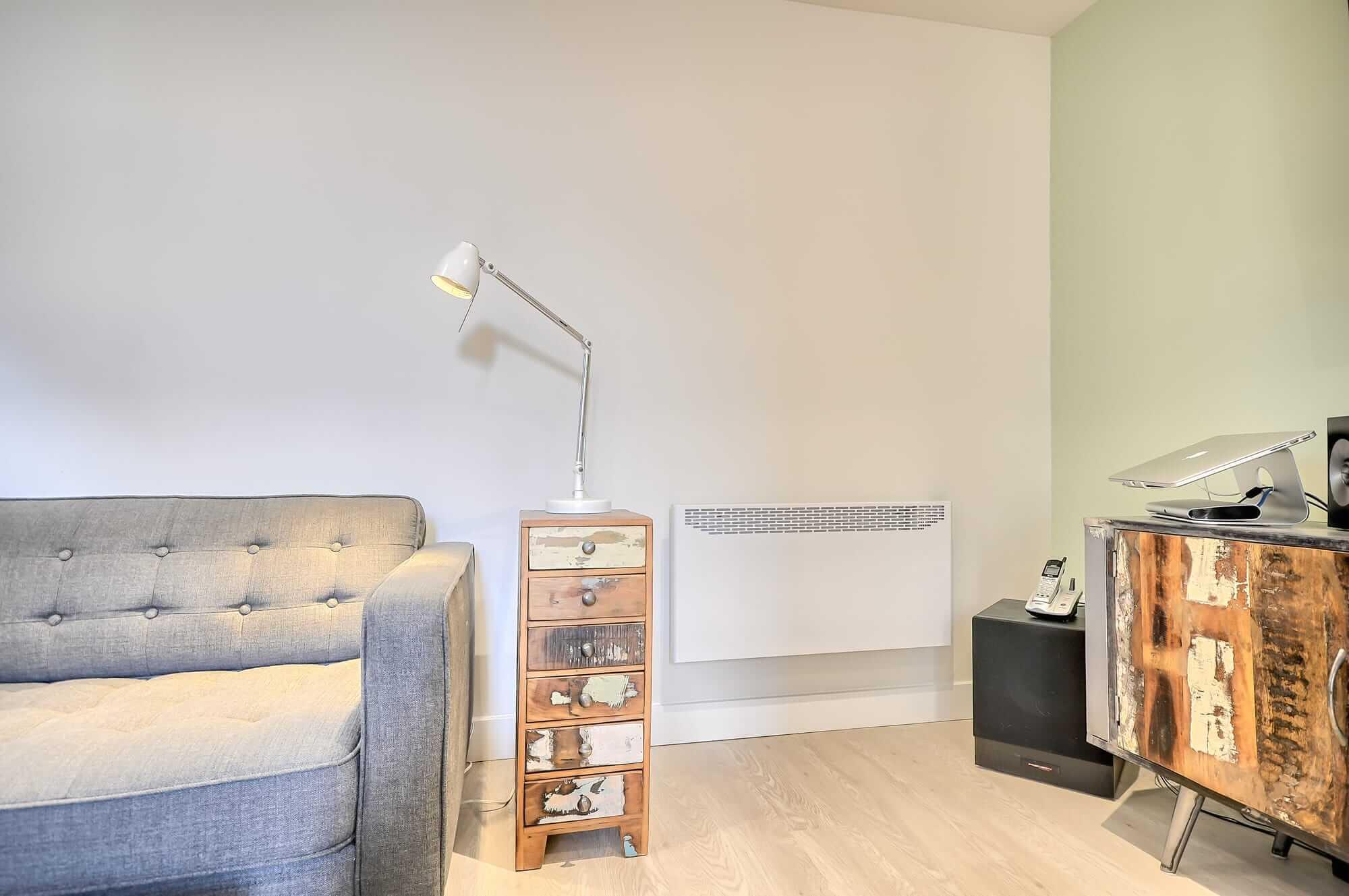 rénovation de sous-sol avec plancher flottant beige, divan gris et mur couleur menthe