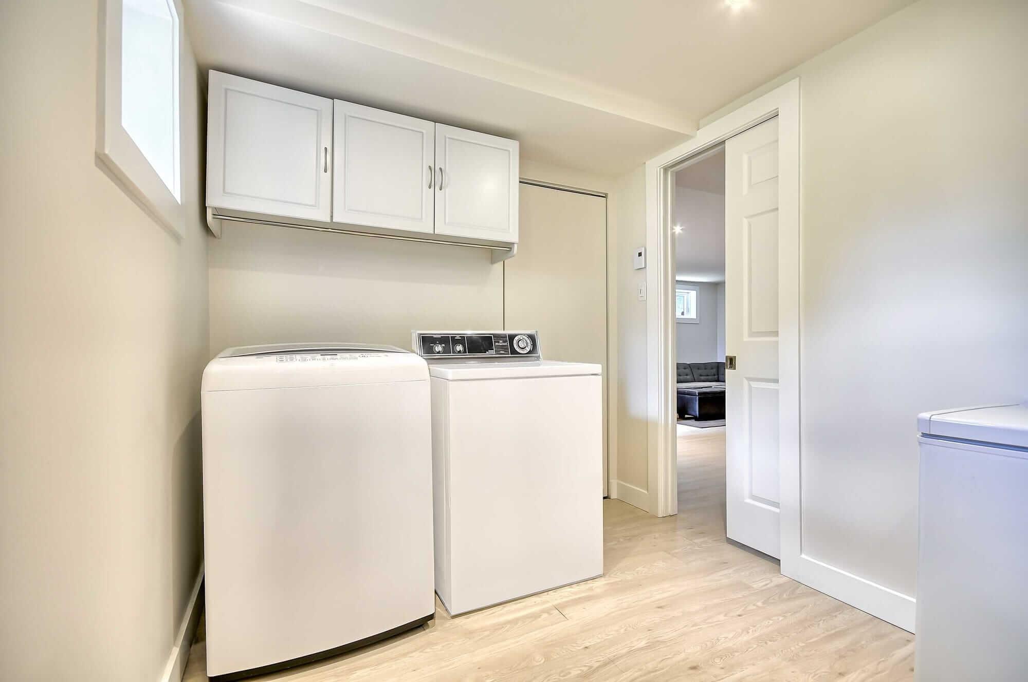 salle de lavage dans un sous-sol rénové avec laveuse-sécheuse et congélateur