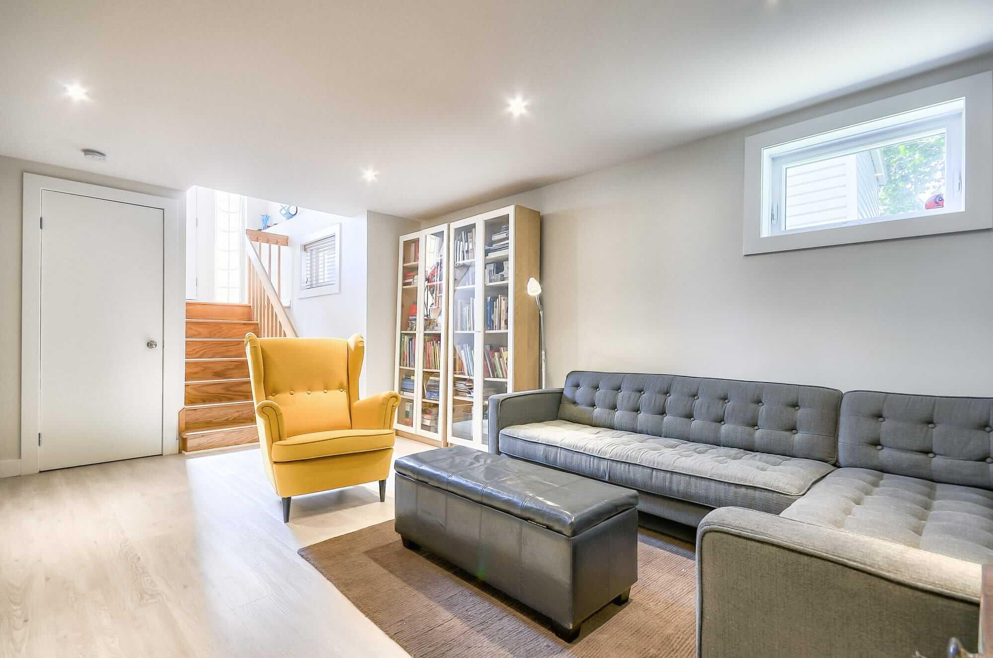 salon au sous-sol avec bibliothèque, fauteuil jaune et divan en L gris