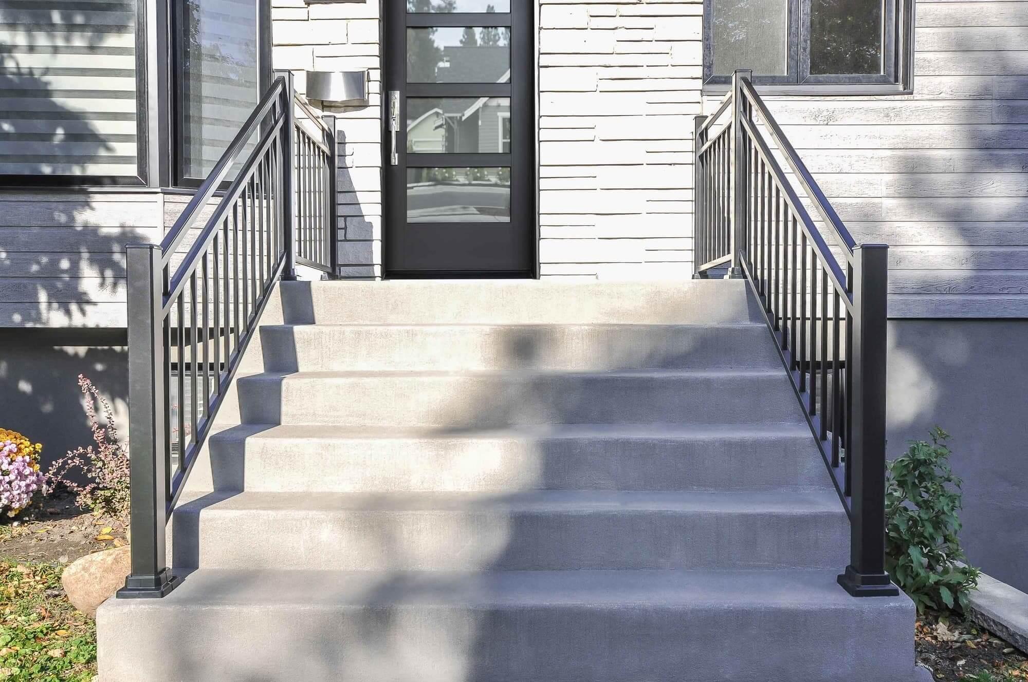 balcon en béton devant d'un bungalow avec rampes noires en aluminium