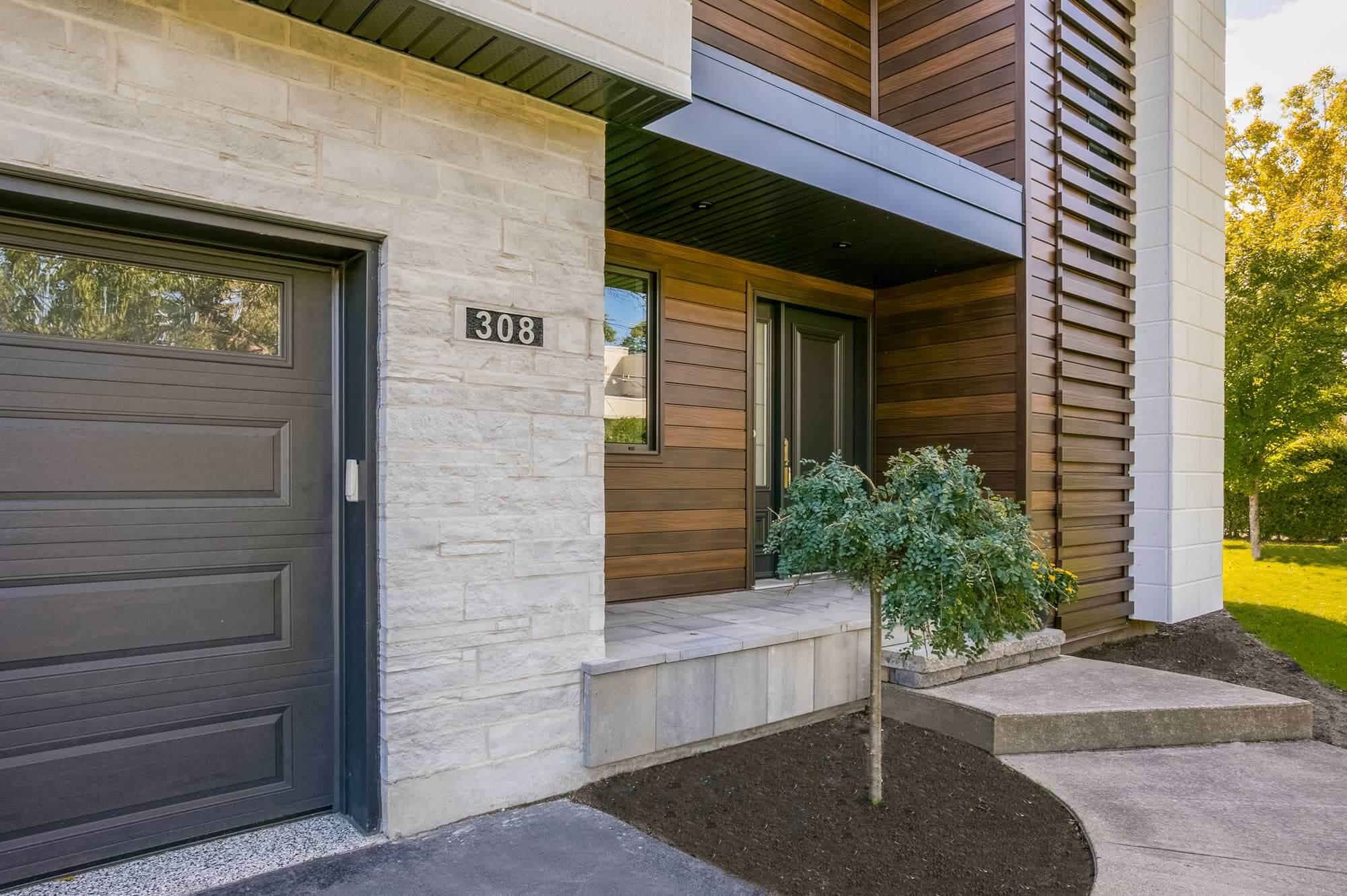 devanture de maison moderne révovée avec un mélange de briques, pierre et bois