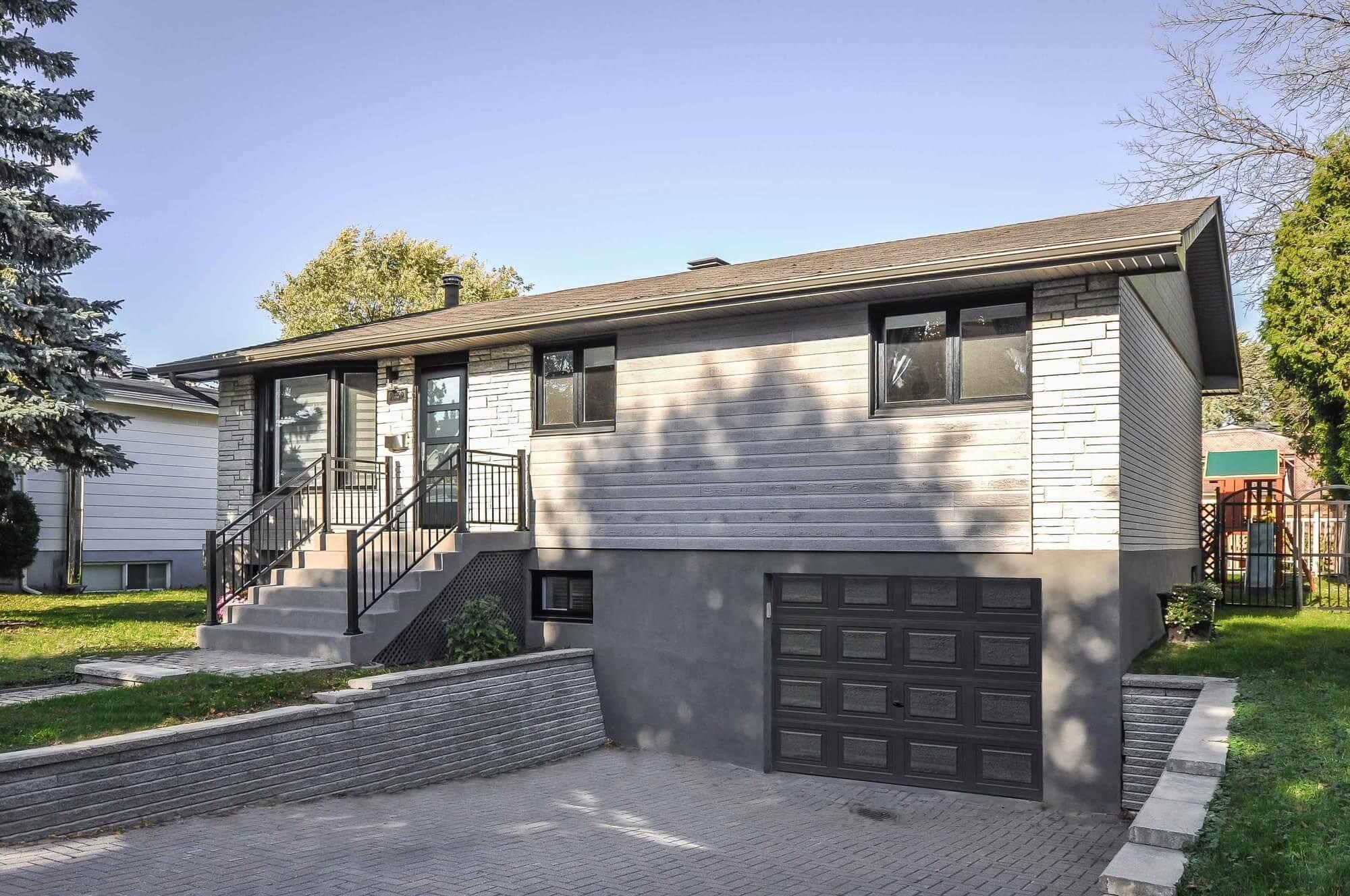 facade de maison nouvellement rénovée avec revêtement en vinyle et briques + nouvelles portes et fenêtres