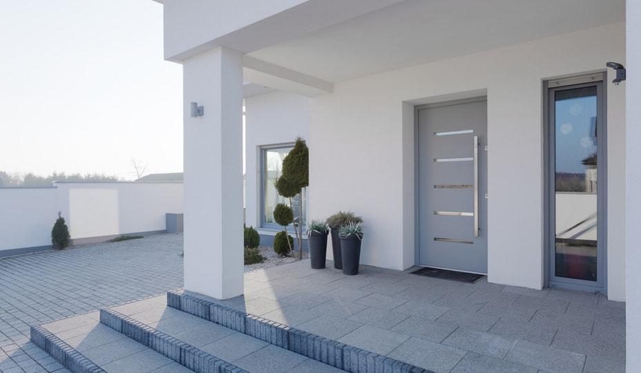 porte d'entrée grise pâle en aluminium avec longue poingnée - maison moderne blanche