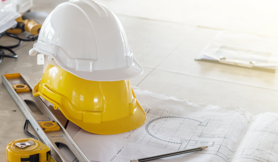 yellow and white hard hat on table with plans