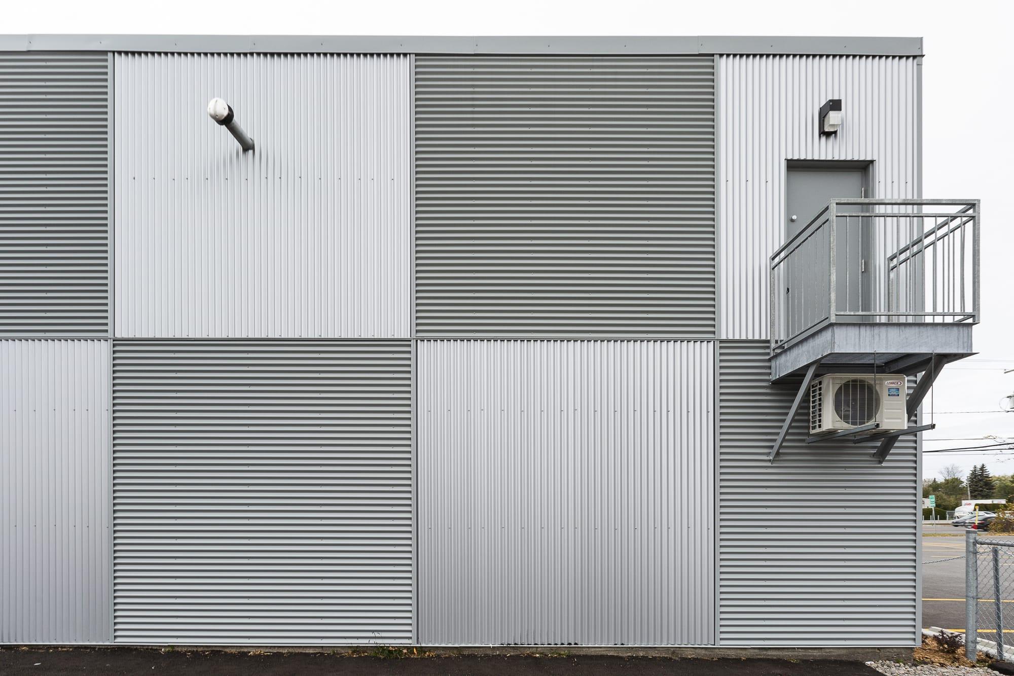 revêtement extérieur bâtisse commerciale - vue arrière avec porte en acier et balcon