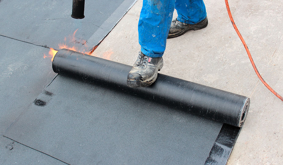 roofer applying a membrane with a blowtorch