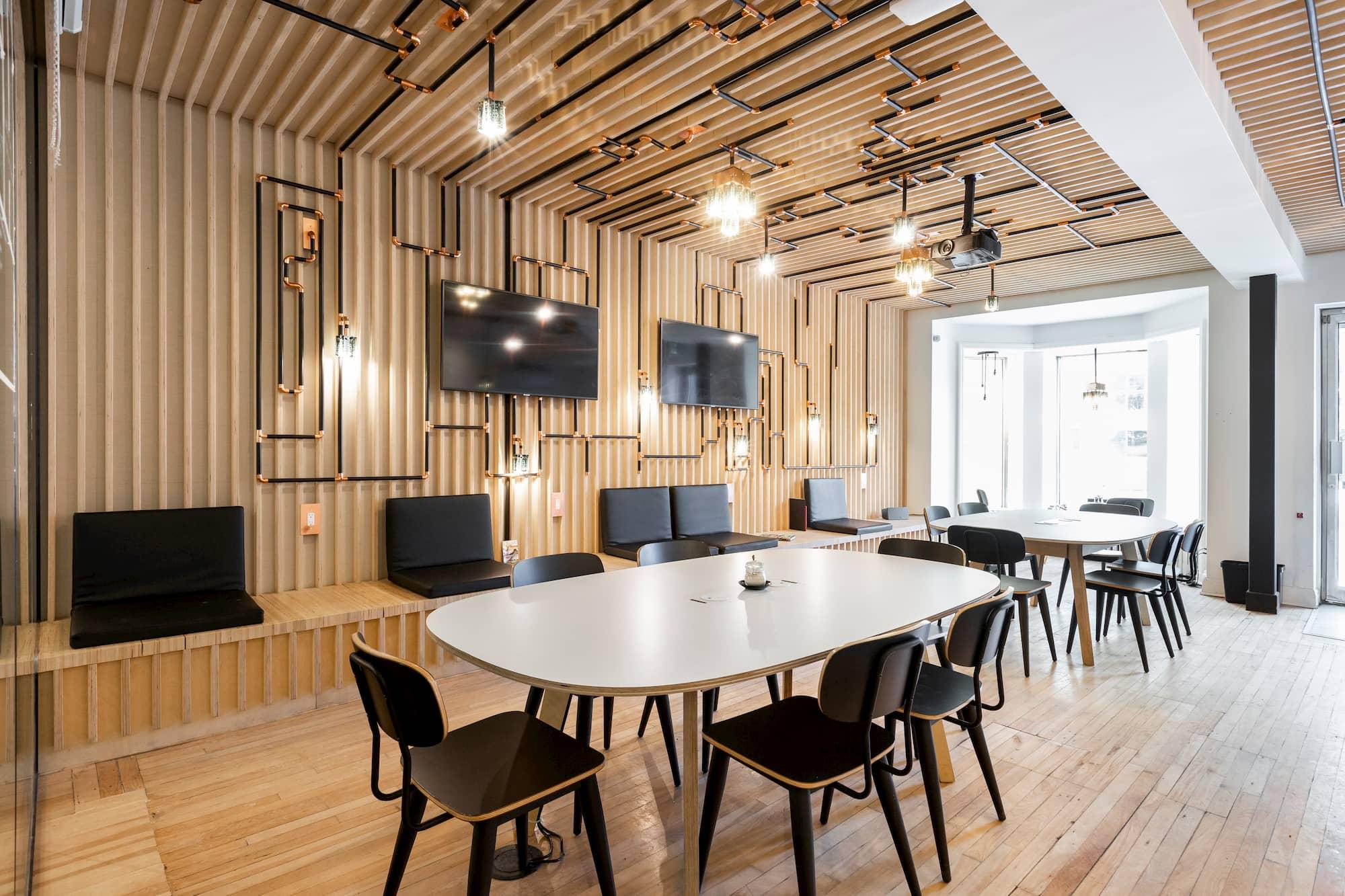 aménagement design d'un café avec tables pâles et chaises noires