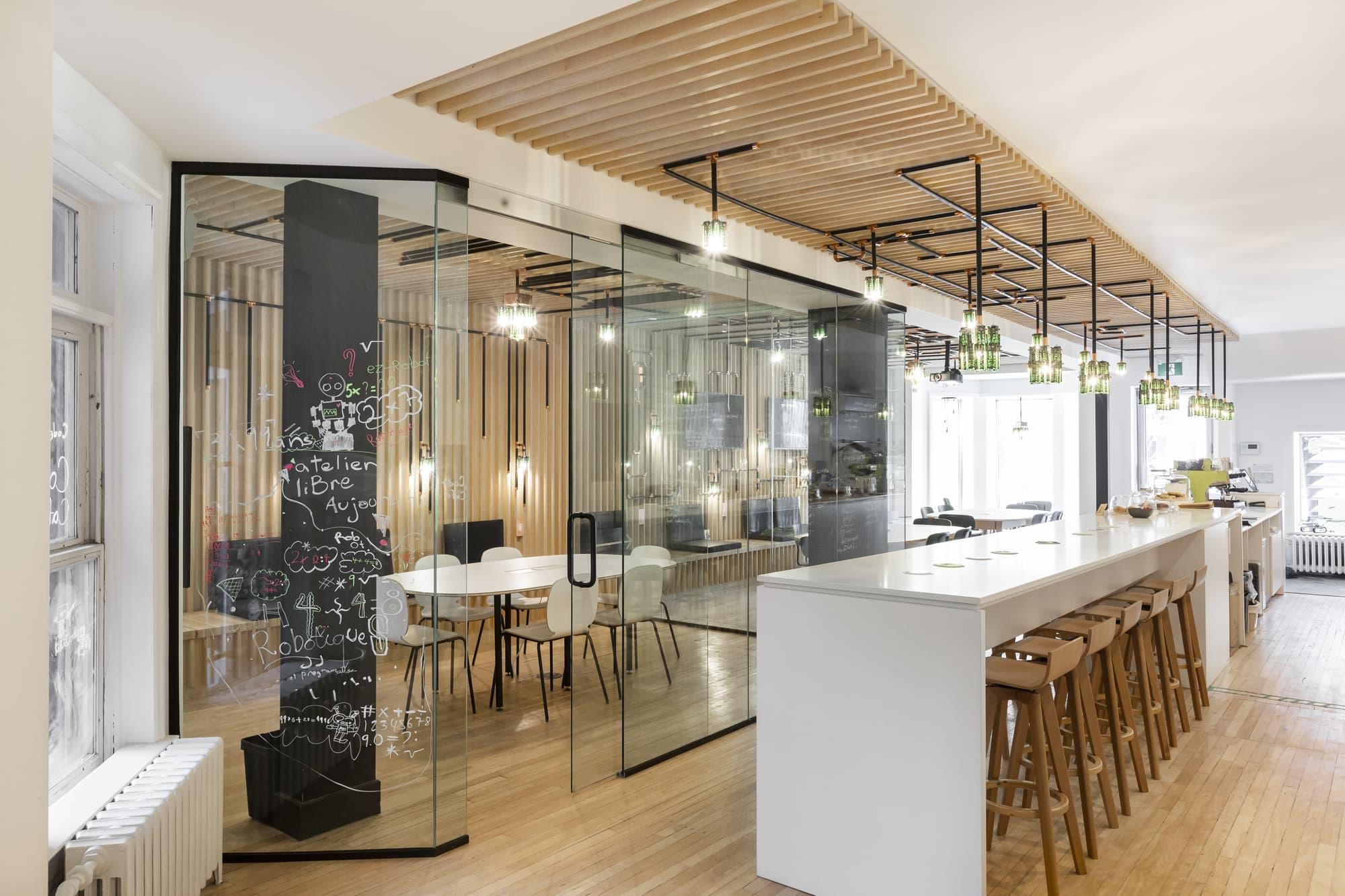 aménagement d'un commerce - café internet avec comptoir de travail blanc et salle de conférence vitrée