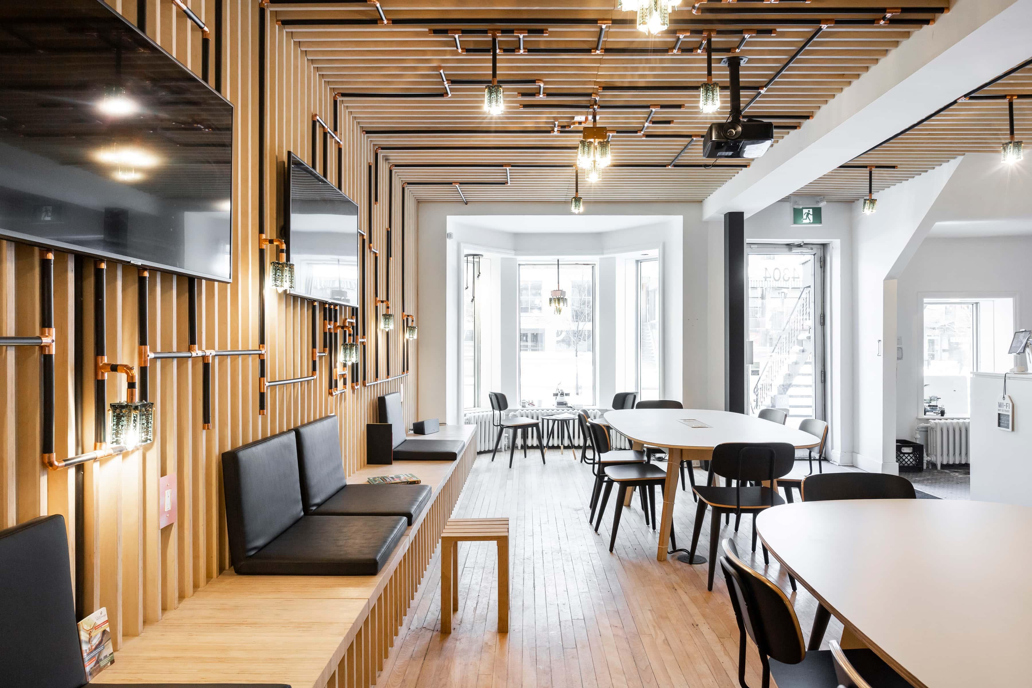 design café branché avec banquettes en bois, sièges noires, téléviseurs au mur et tables en bois pâle