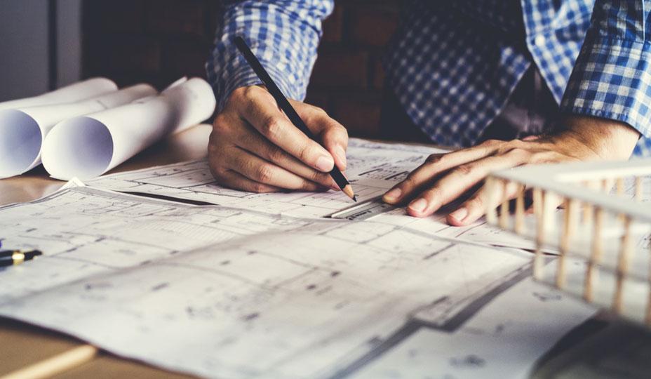 architecte qui dessine agrandissement de maison pour évaluer le cout