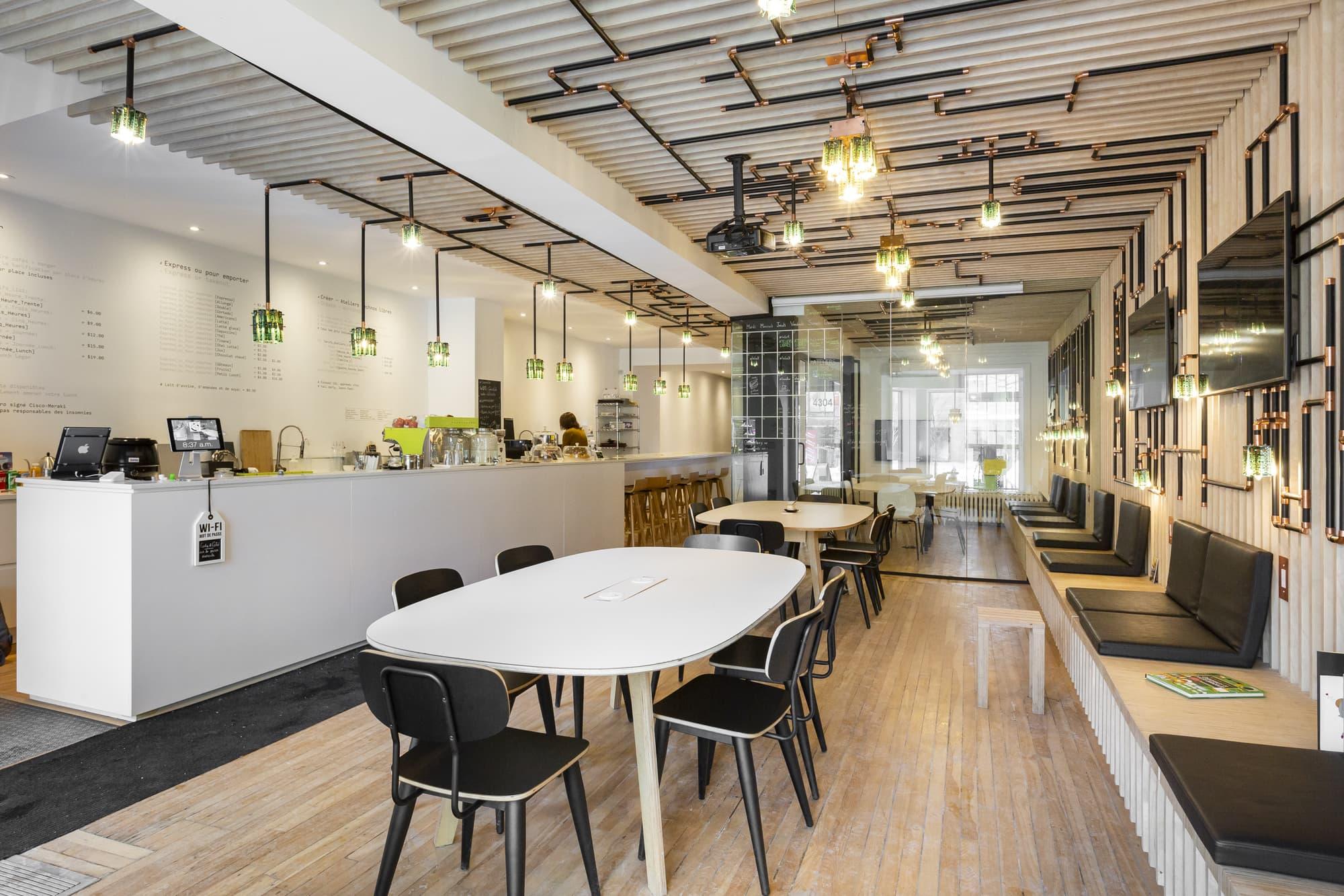 rénovation commerciale d'un café multifonctionnel - vue sur le comptoir blanc avec tables beiges