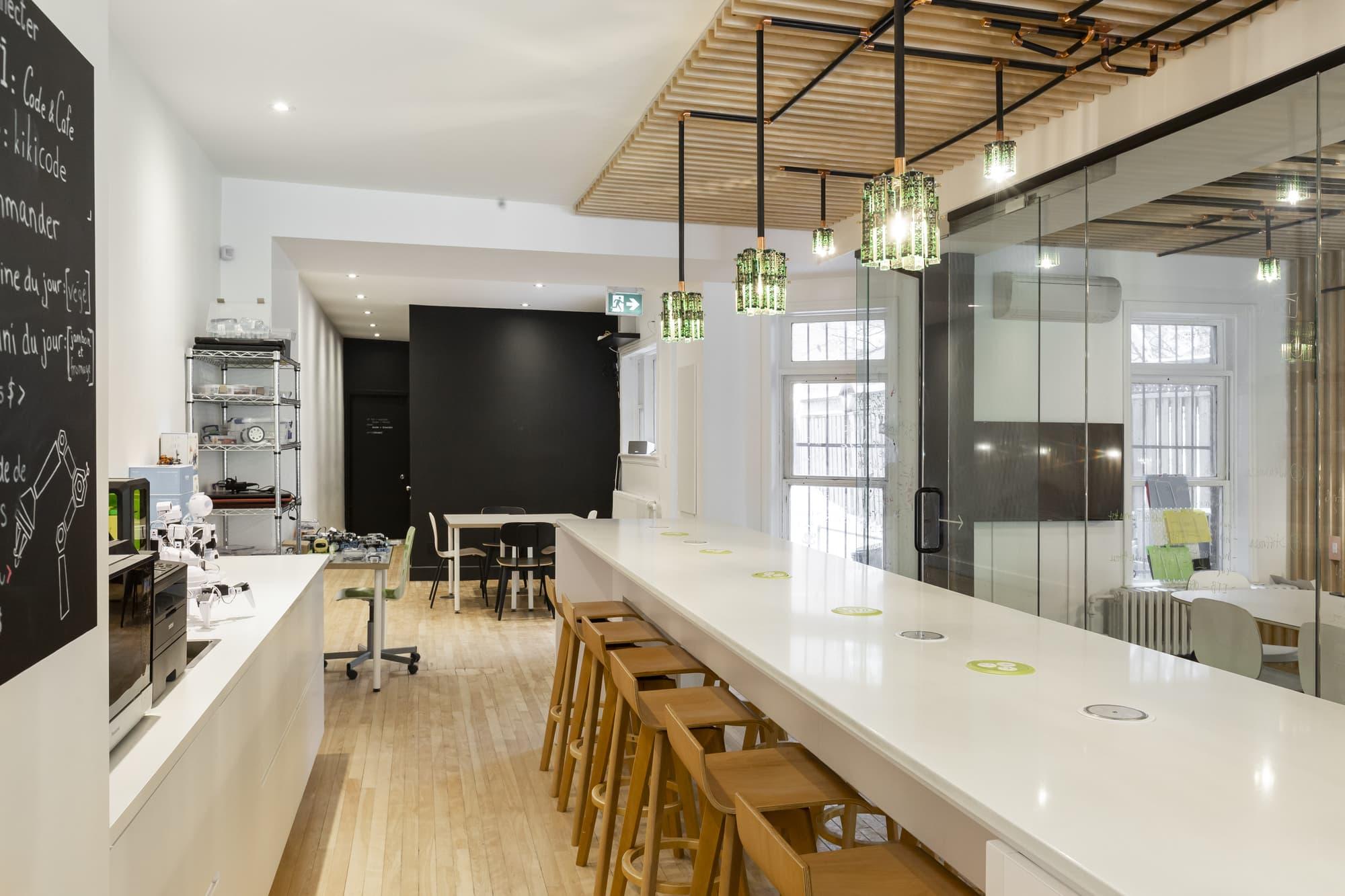 renovation local commercial - café branché multifonctionnel avec comptoirs blancs et tableau de menu noir