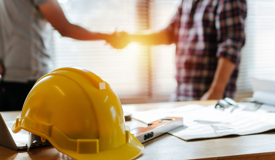 two people shaking hands on a construction site