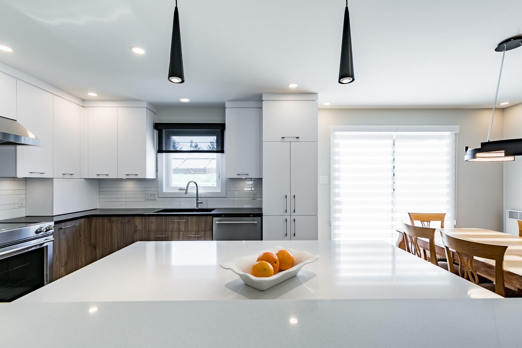 cuisine design deux tons avec îlot et comptoirs en quartz