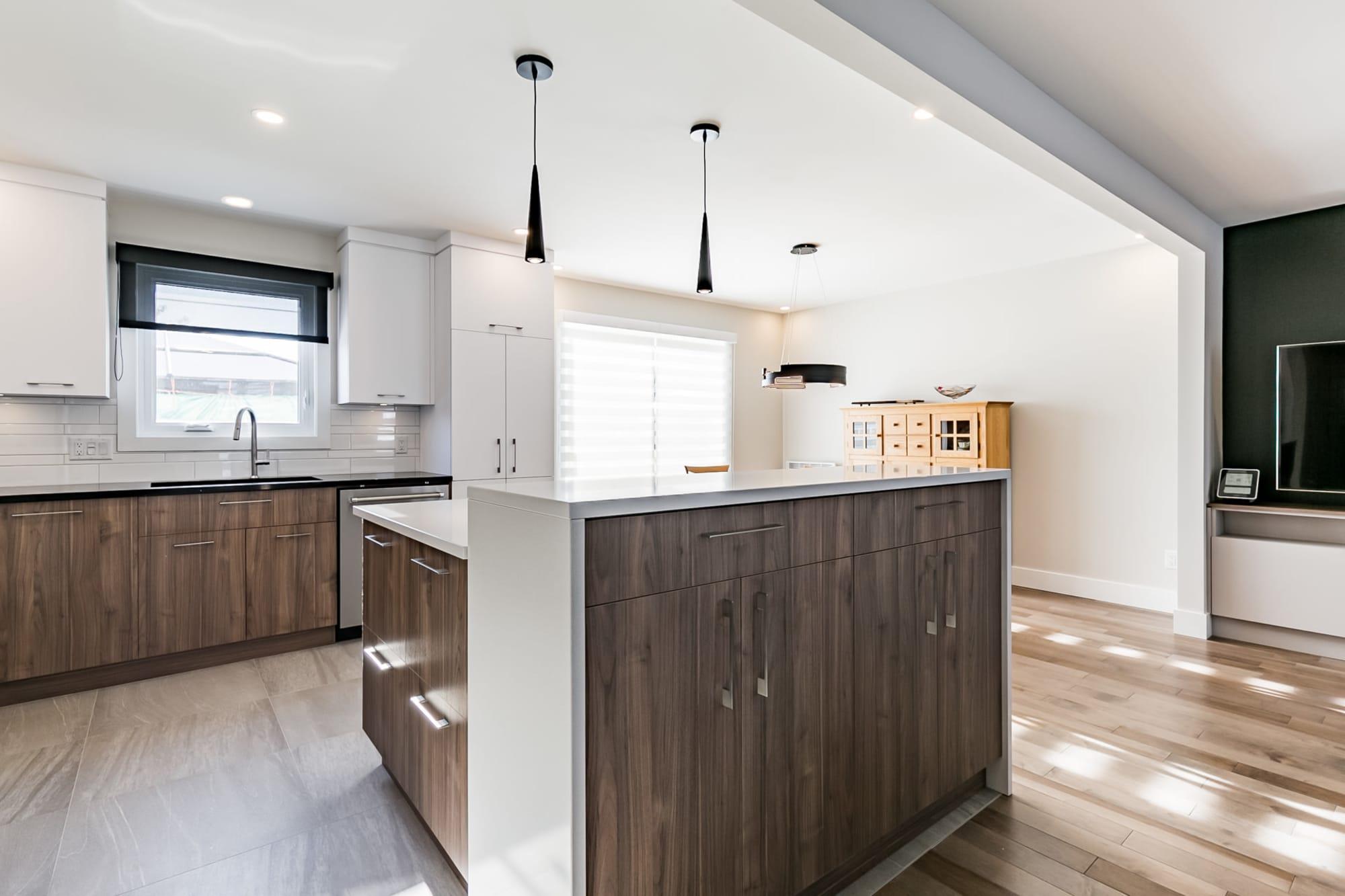 cuisine ouverte de style contemporain avec cabinets deux tons et comptoir en quartz