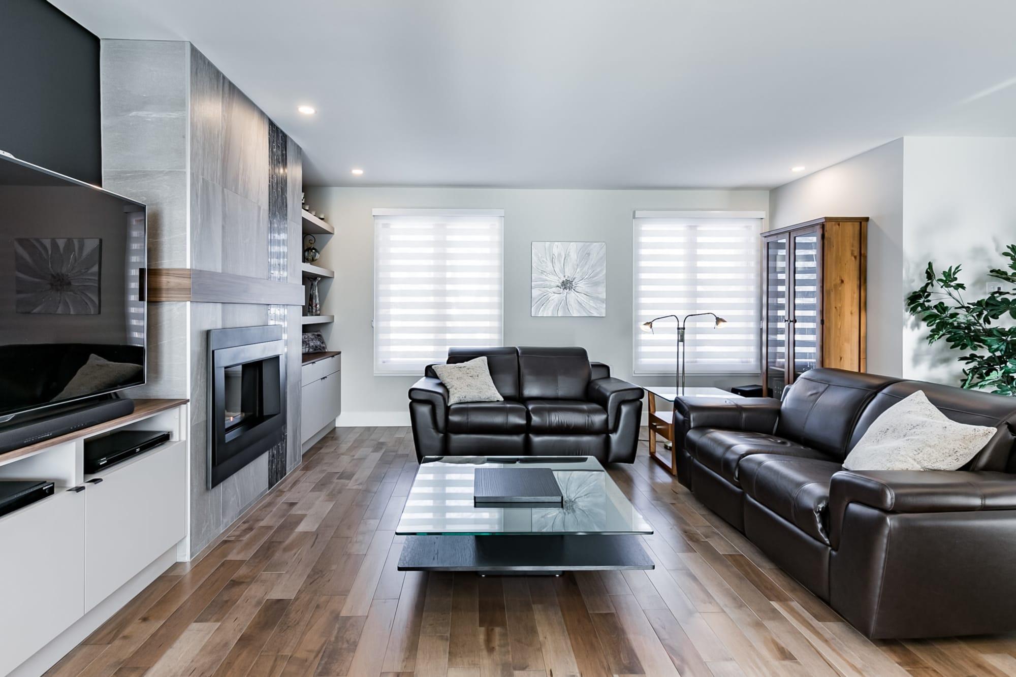 salon design avec plancher en bois franc, foyer et meuble sur mesure
