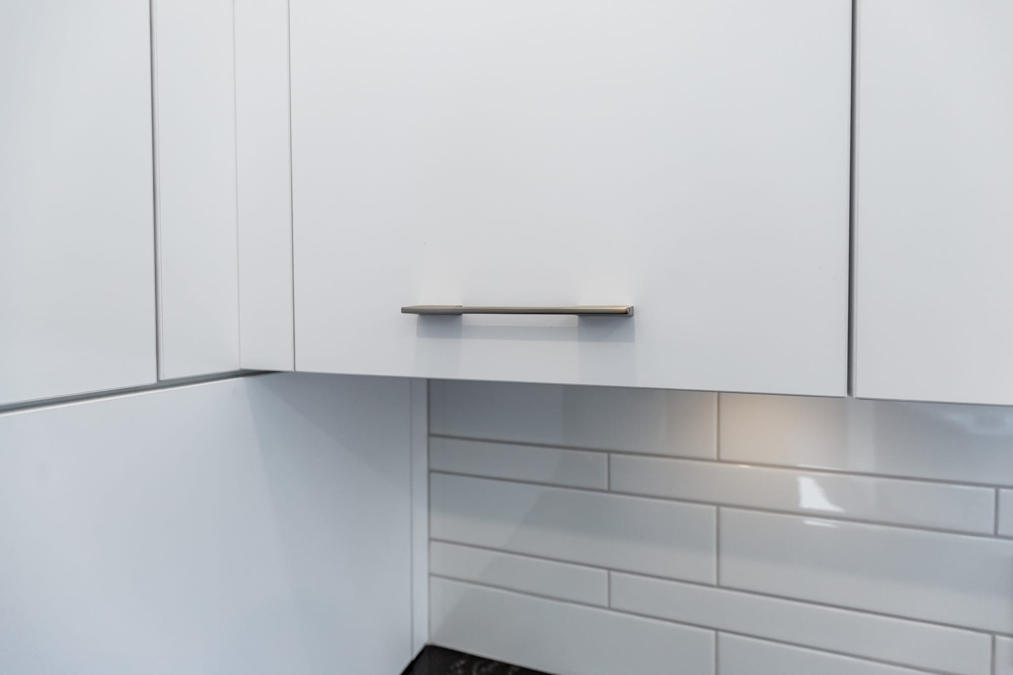 white melamine cabinets with a ceramic backsplash