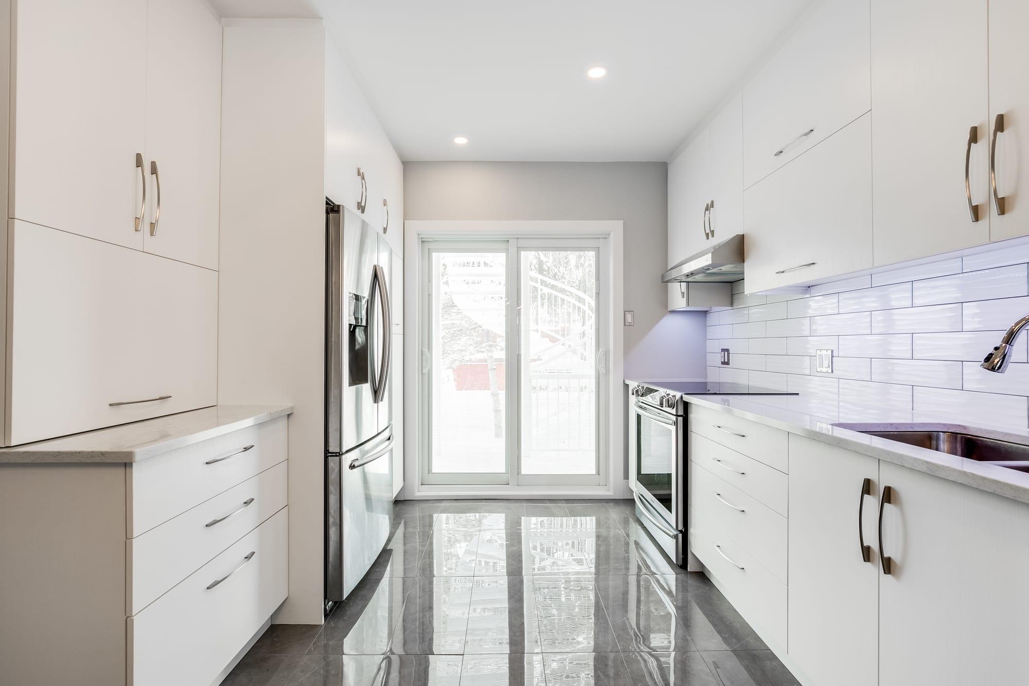 cuisine moderne avec armoires blanches et revêtement de plancher en céramique