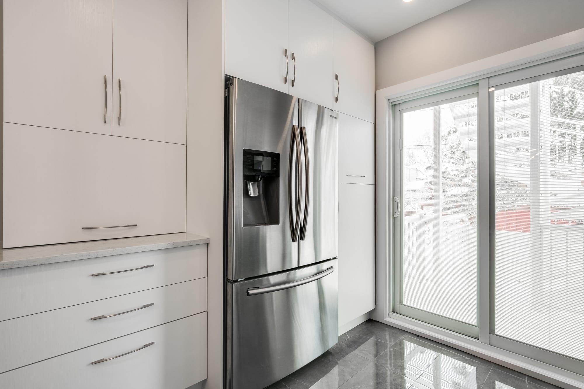 design cuisine avec armoires blanches et réfrigérateur en stainless
