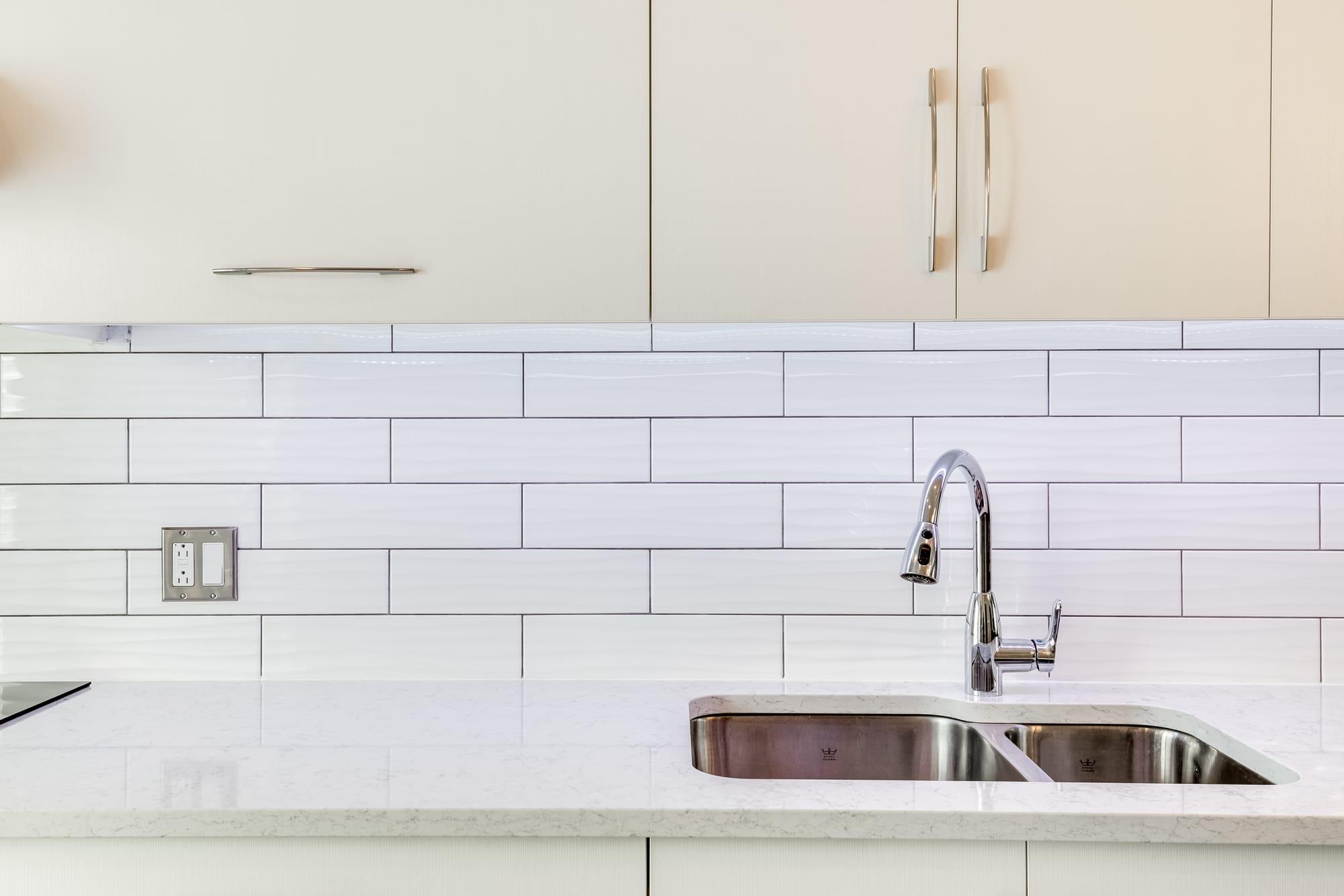 dosseret de cuisine en céramique blance avec lavabo et robinet en stainless