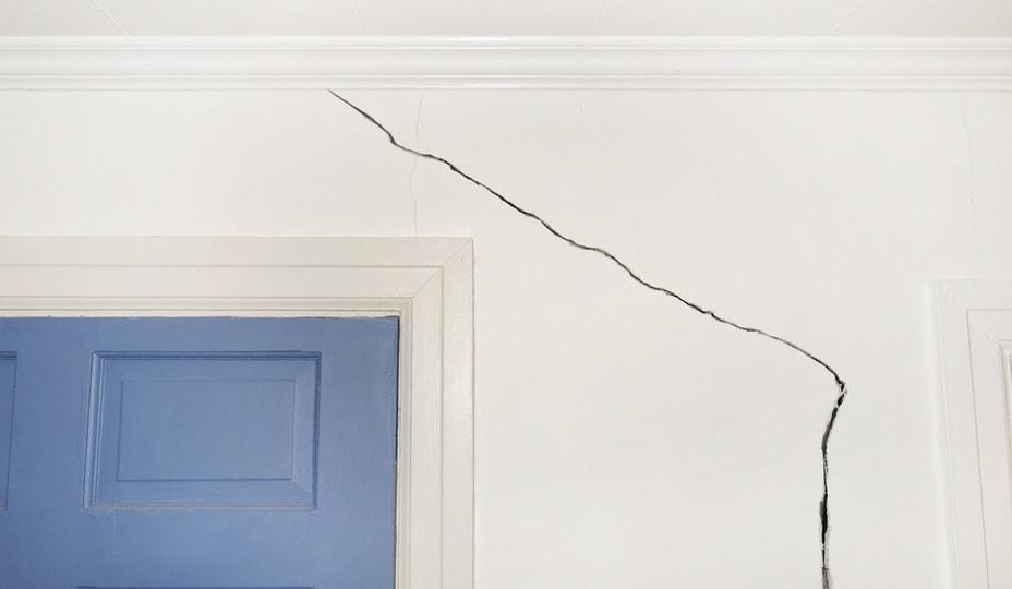 fissure sur un mur blanc à l'intérieur d'une maison avec porte bleue