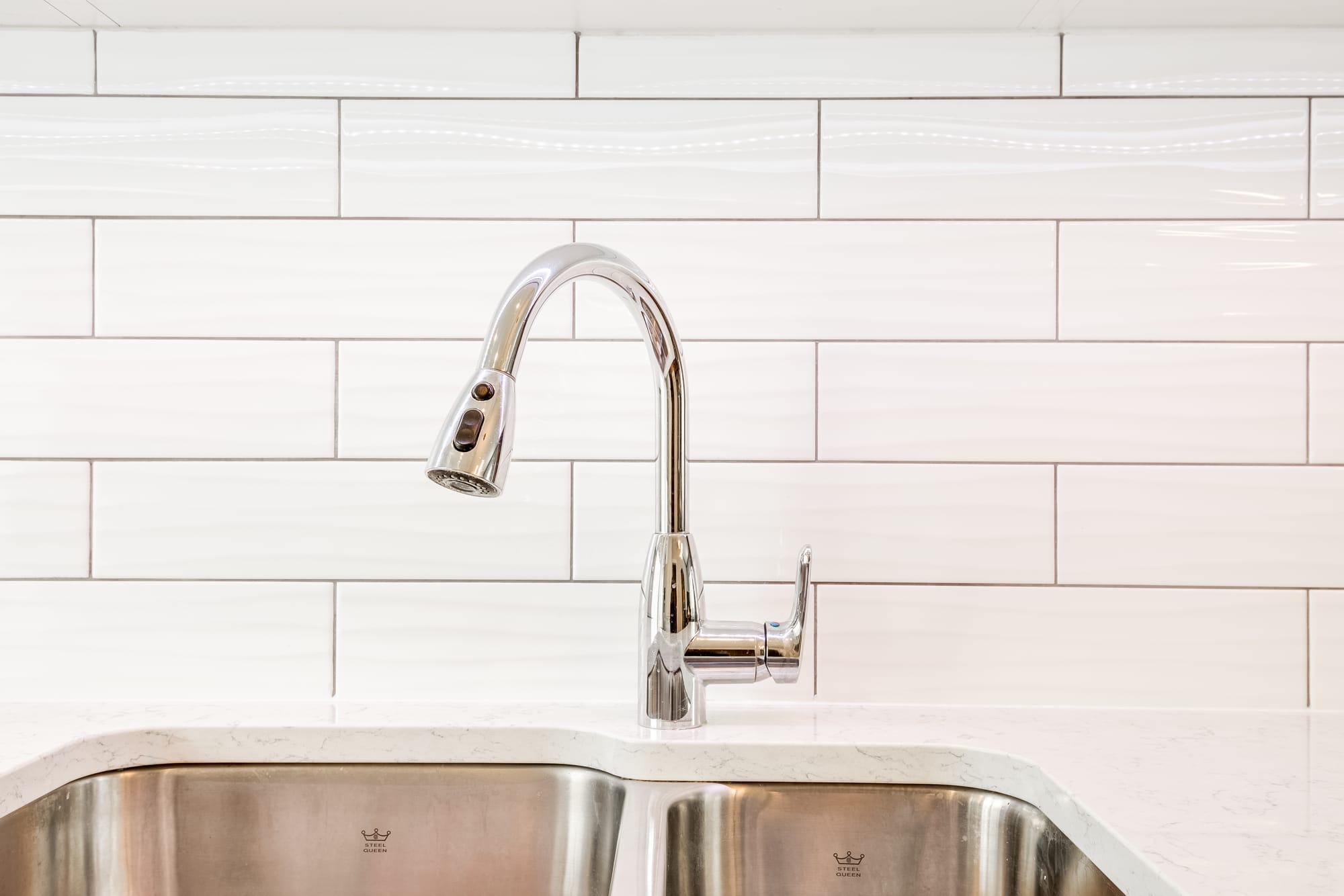 kitchen faucet with a white backsplash