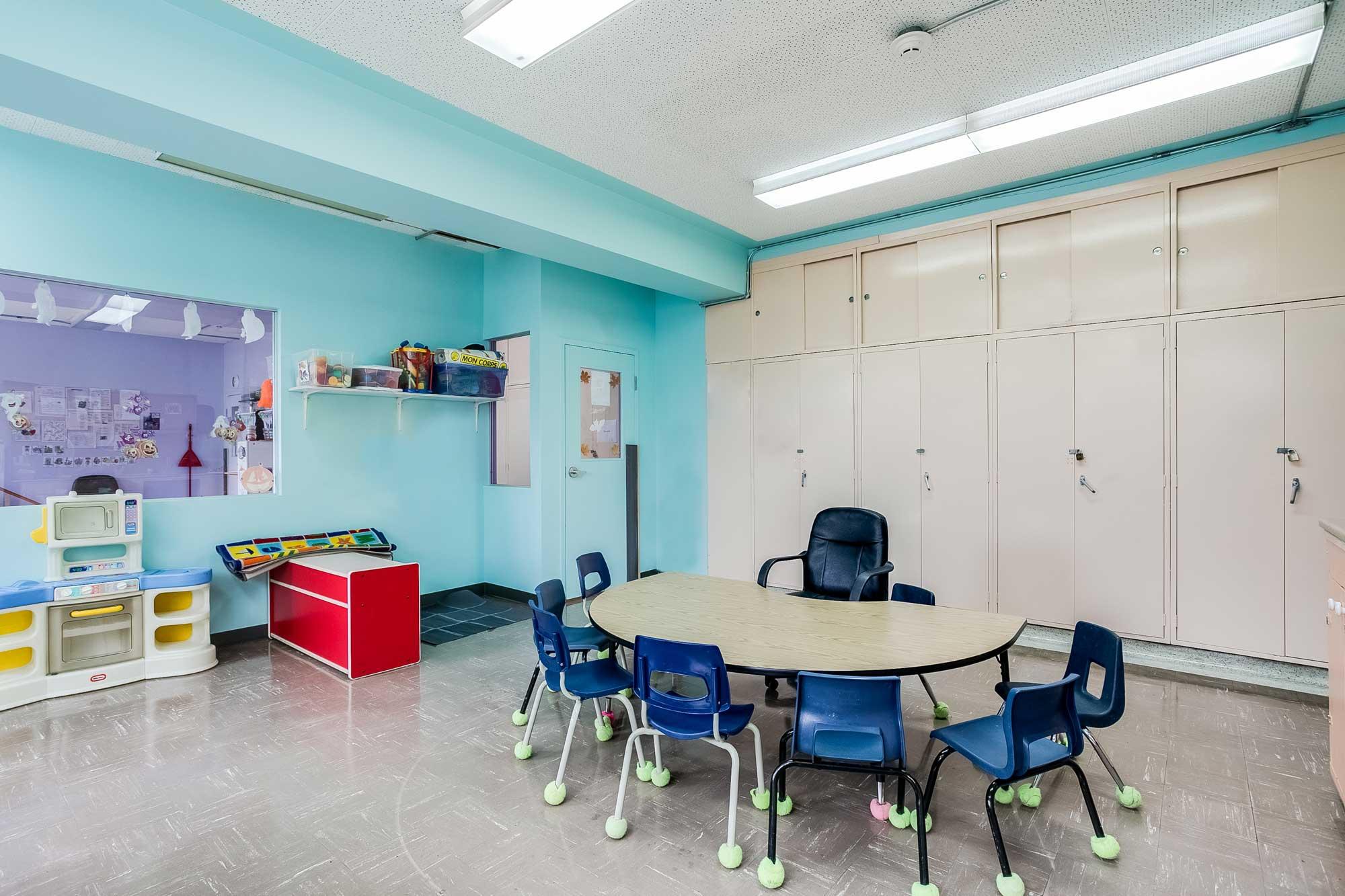 local de garderie rénové avec table, chaises et armoires qui barrent
