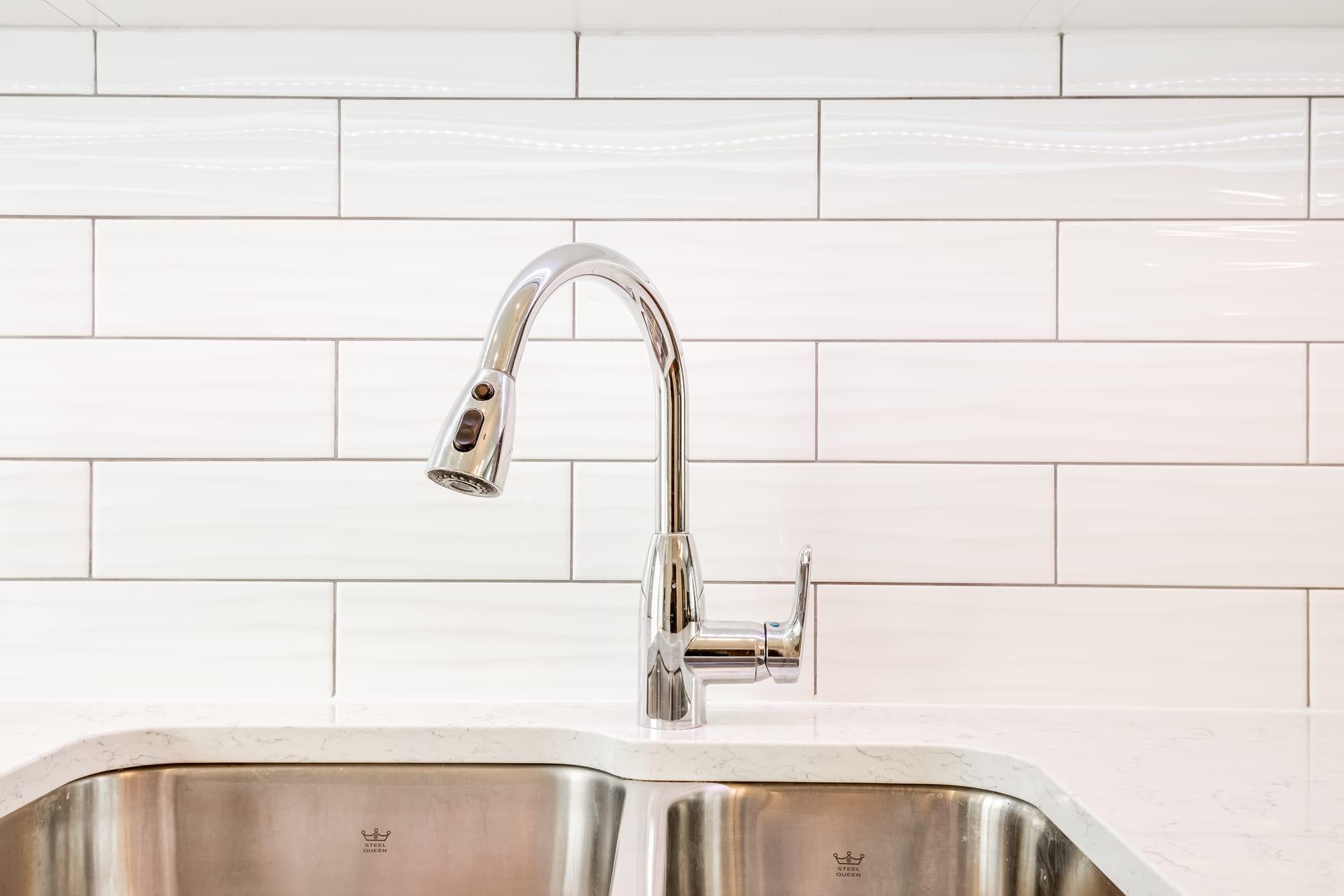 robinet de cuisine de couleur argent avec dosseret en céramique blanc