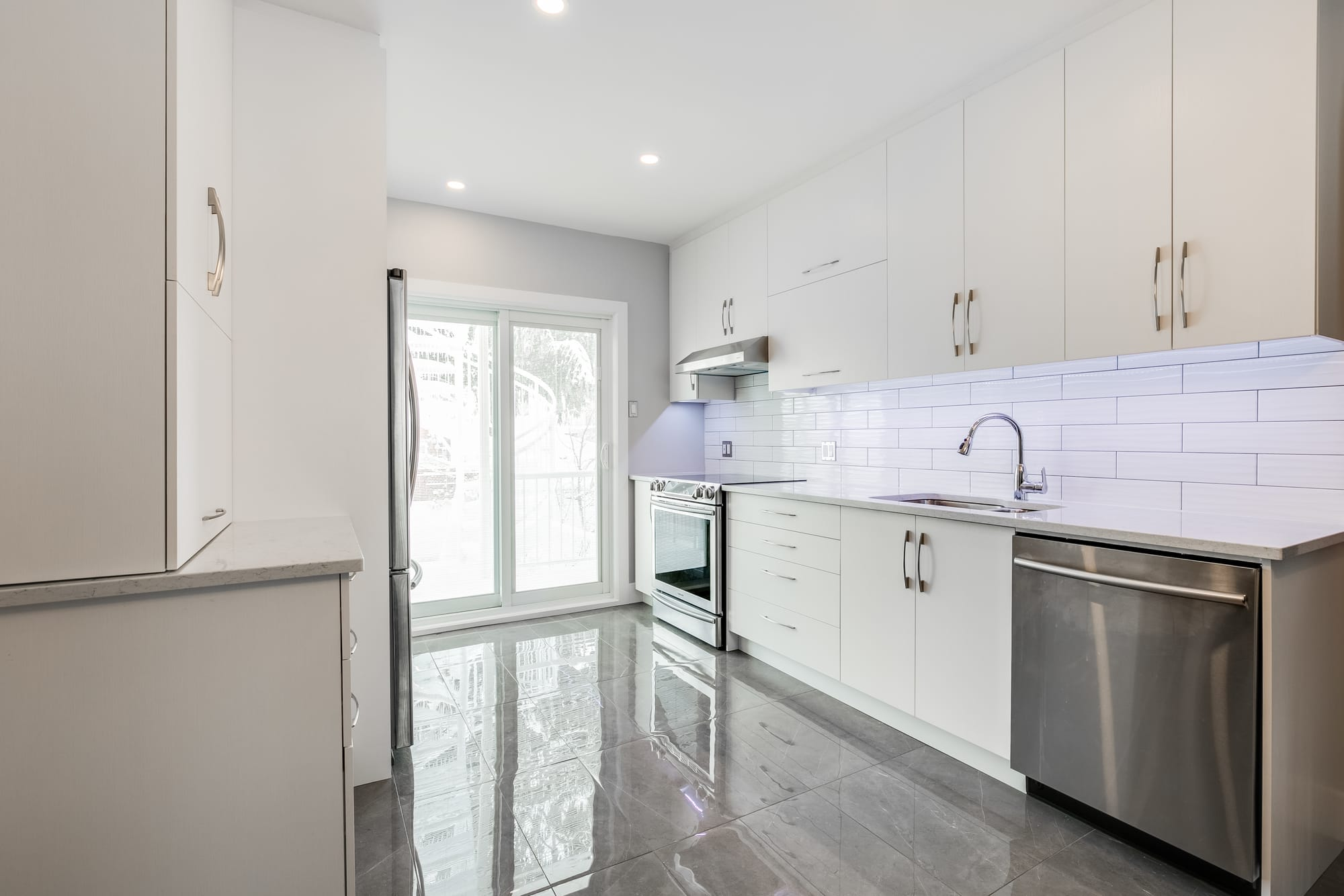 white kitchen with grey ceramic floor and a stainless steel dishwasher