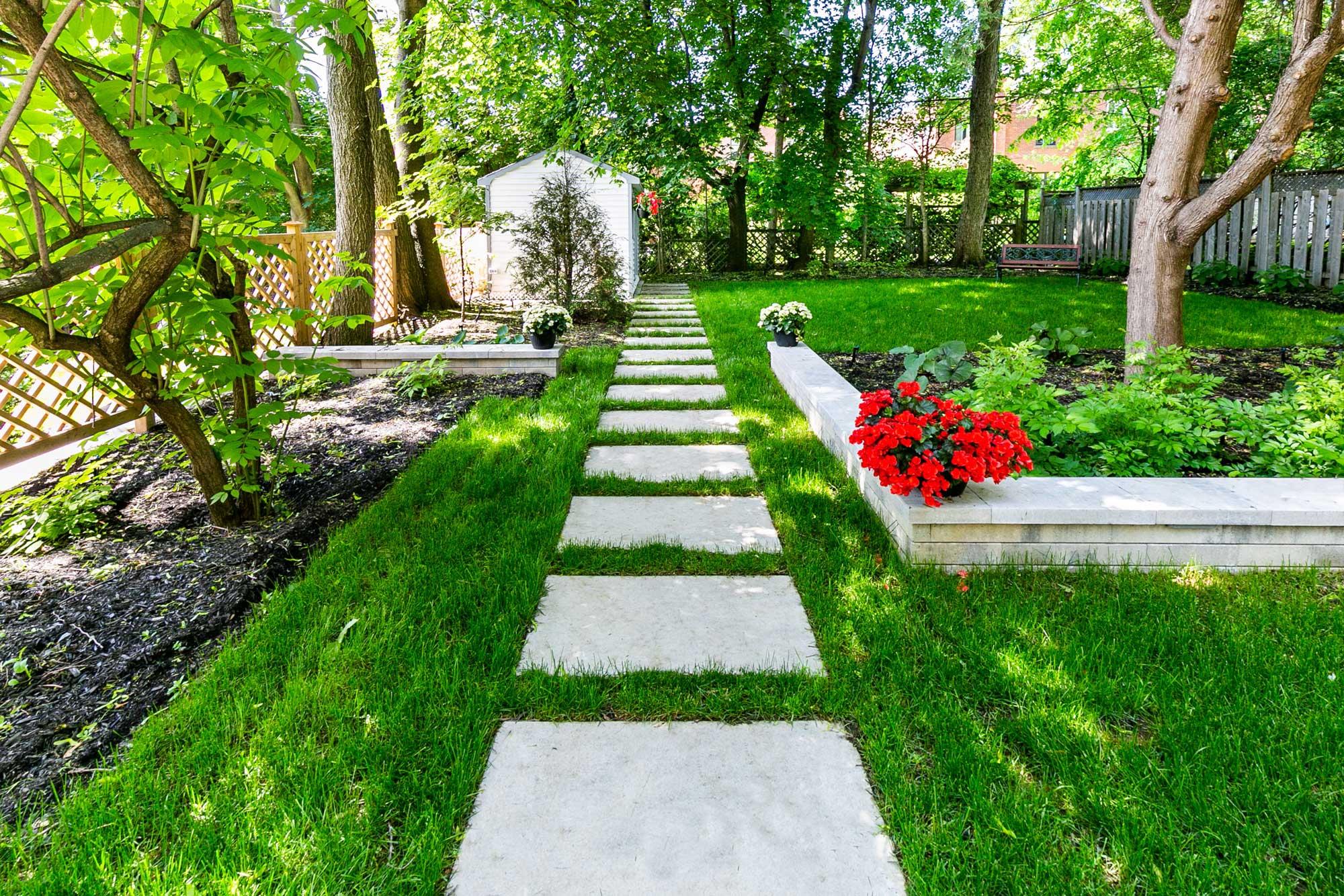aménagement paysager dans une cour arrière avec dalles de béton et fleurs rouges