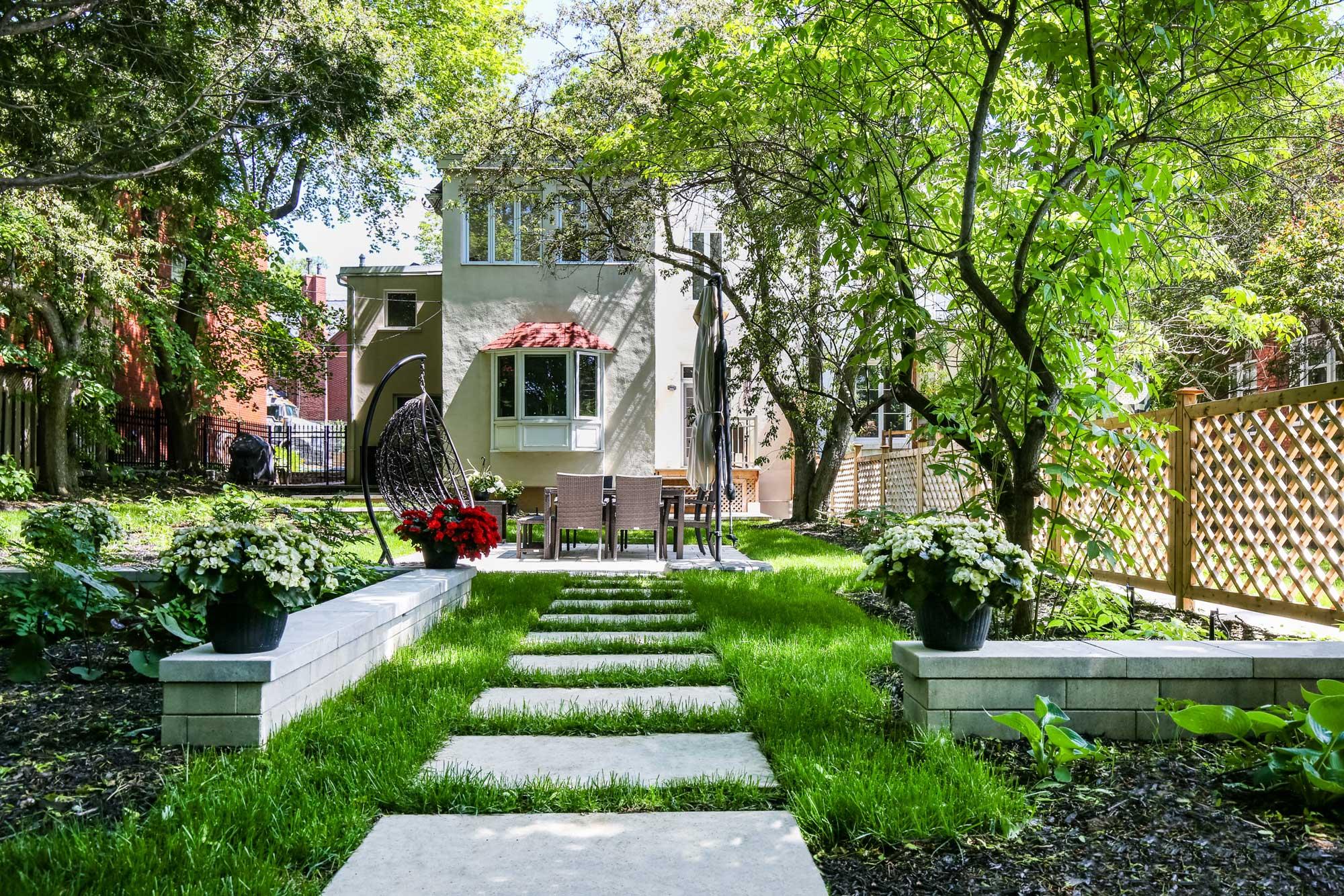 aménagement extérieur d'une cour arrière avec terrasse, table, dalles de jardin en béton et clôture en bois