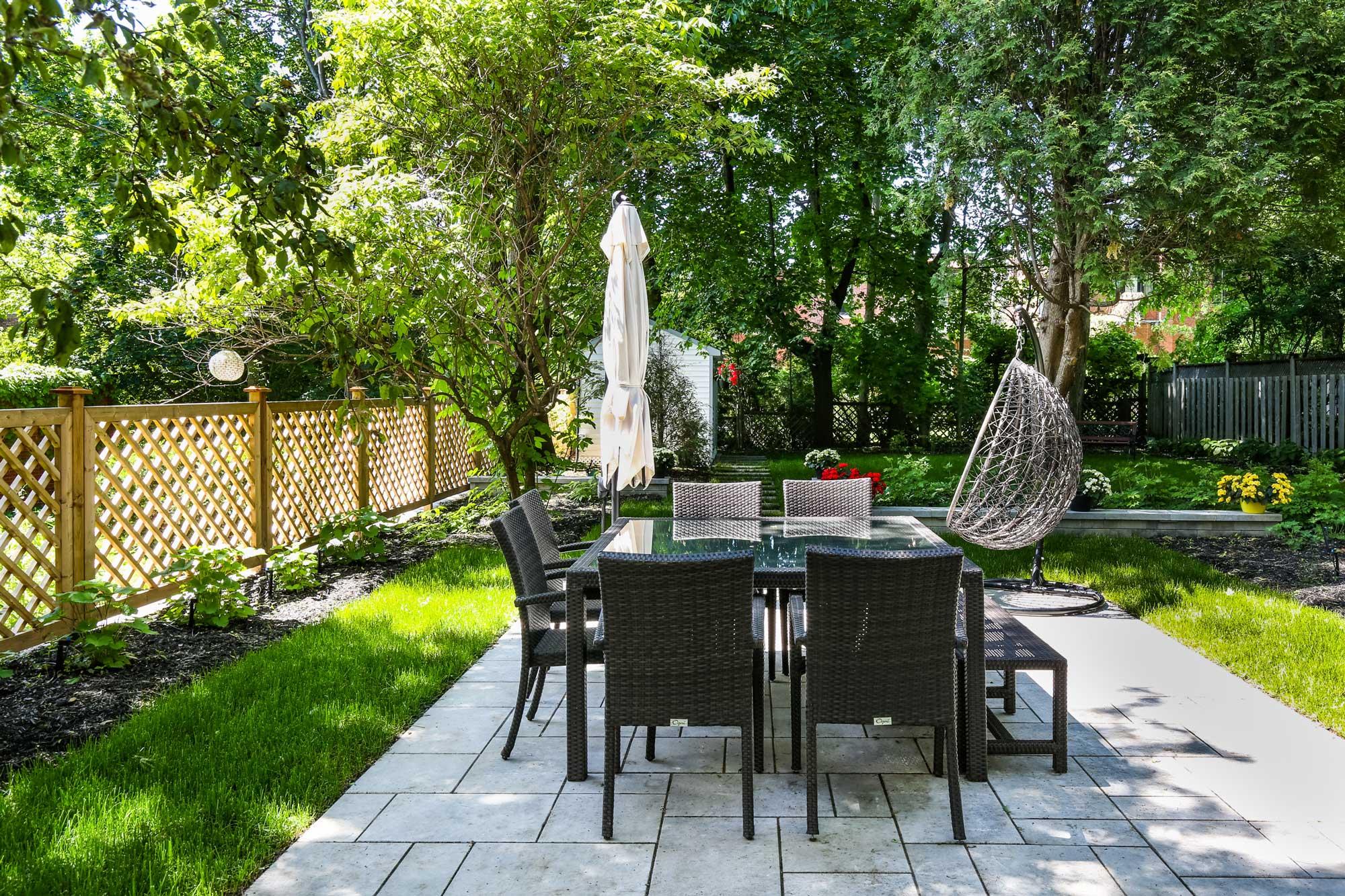 aménagement d'une terrasse dans une cour arrière avec table, parasol fermé et clôture en bois