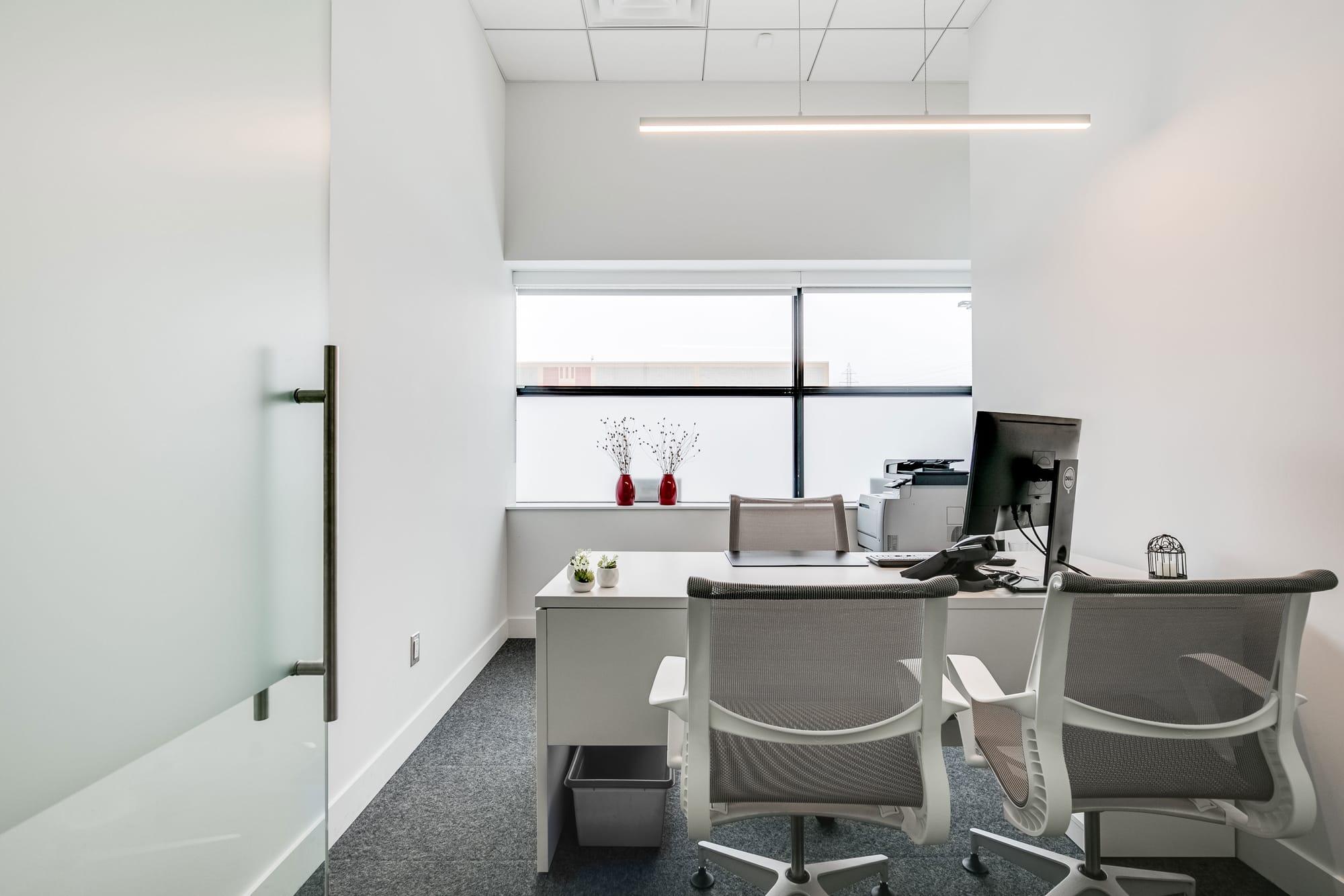 bureau moderne rénové avec chaises blanches et vue sur une grande fenêtre