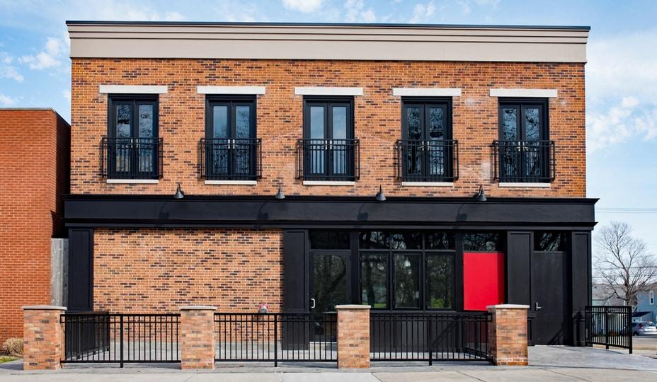 commerce en briques brunes pâles deux tons avec fenêtres et portes noirs