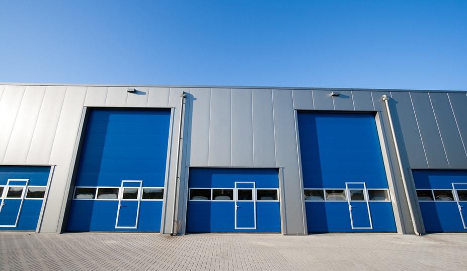 façade d'un édifice industriel avec portes de garage bleues et revêtment en aluminium gris