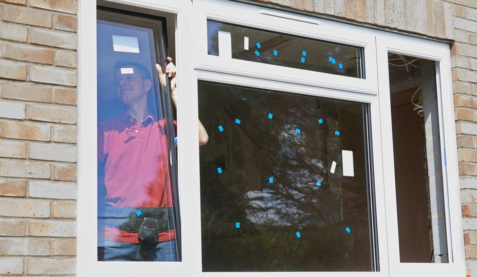 entrepreneur qui installe fenêtres de l'intérieur