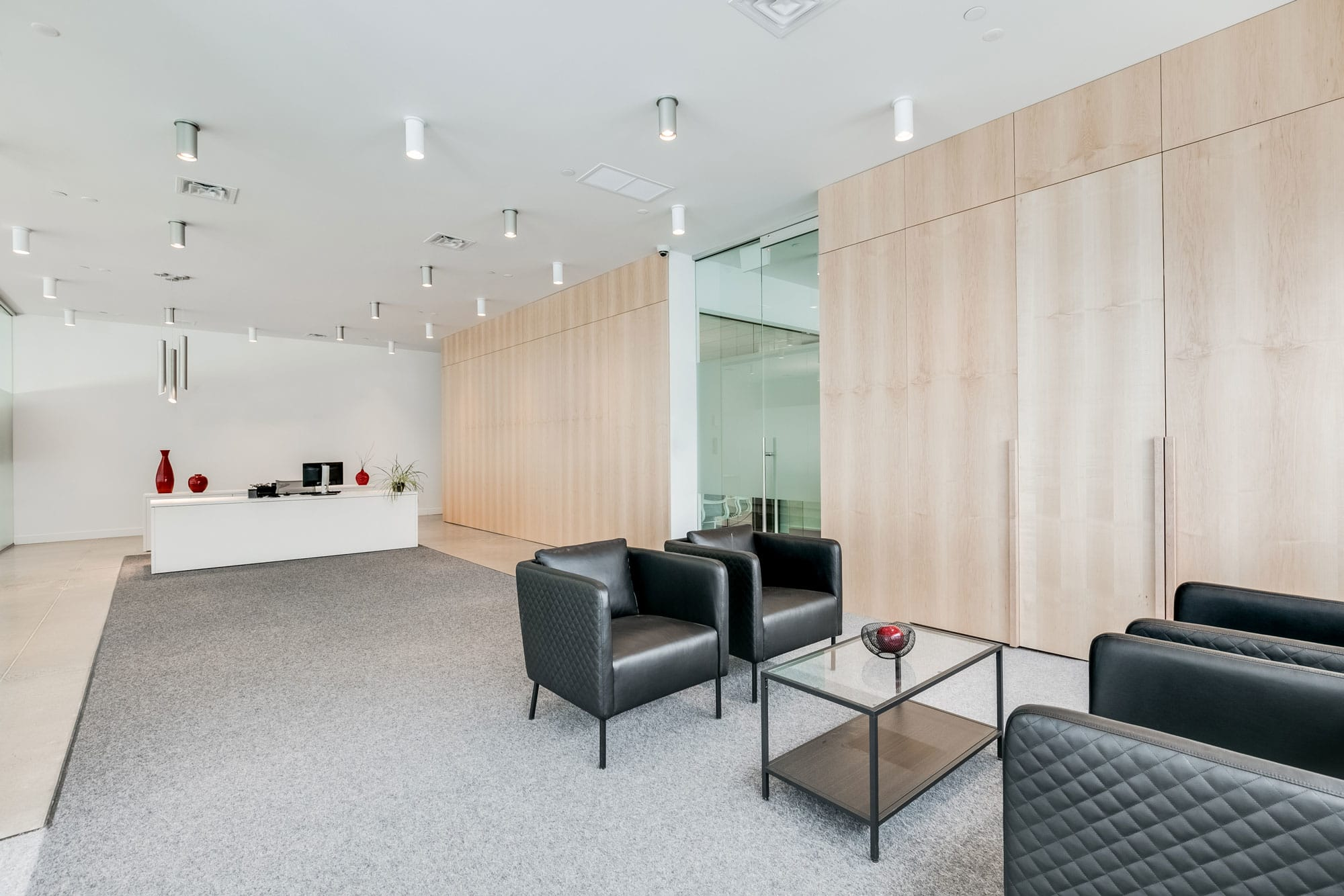 office reception with black armchairs and a wooden wall